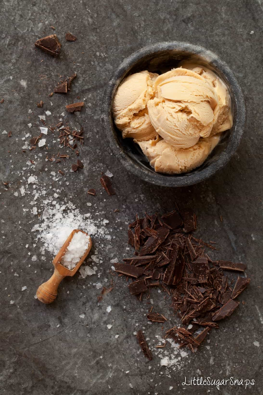 A bowl of salted caramel ice cream with dark chocolate and sea salt alongside