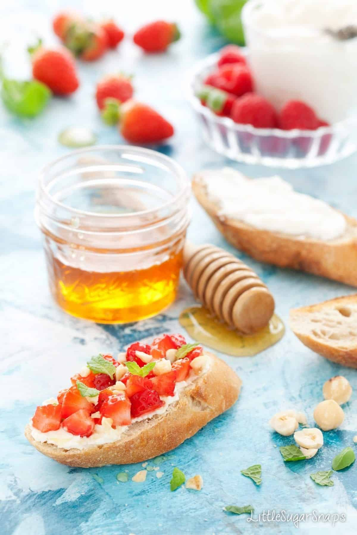 Toasted baguette slice topped with soft cheese, strawberries, hazelnuts and mint