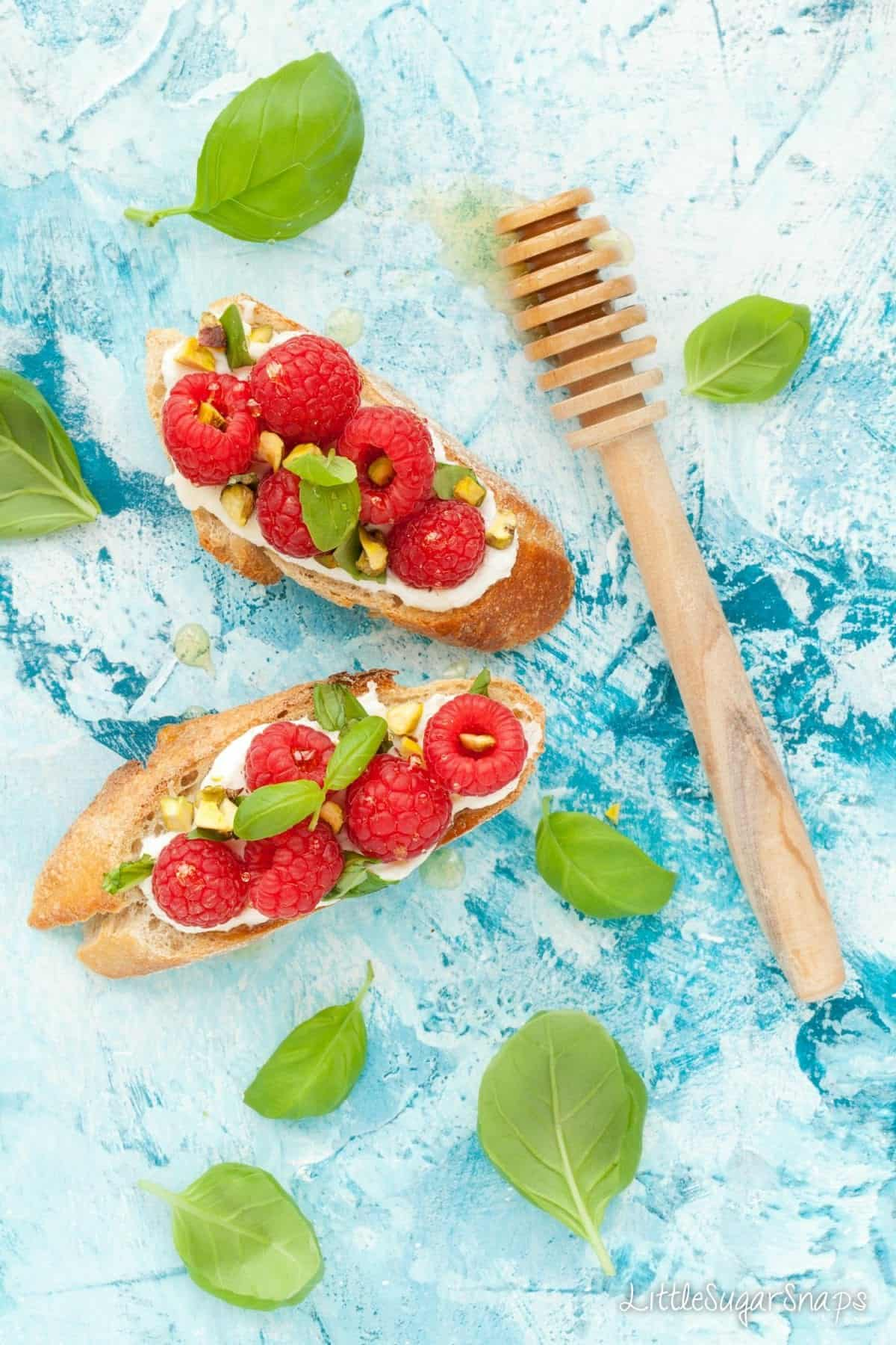 Overhead of toasted baguette topped with soft cheese, raspberries, pistachio and basil