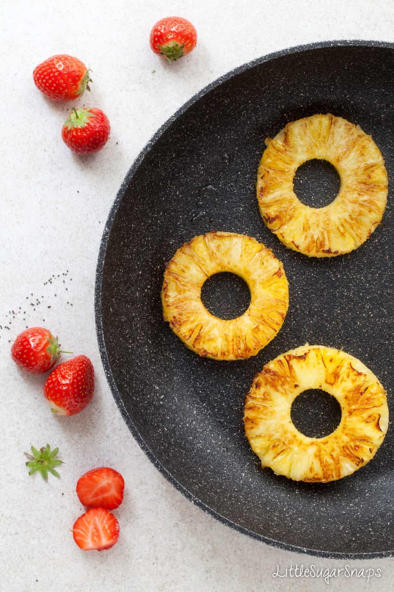 Frying pineapple rings in a pan