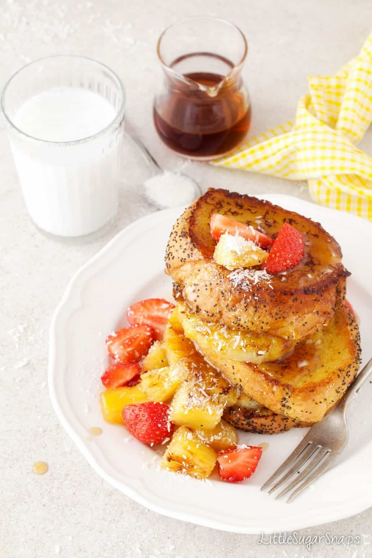 Vegan French Toast stacked up with fresh pineapple and strawberries