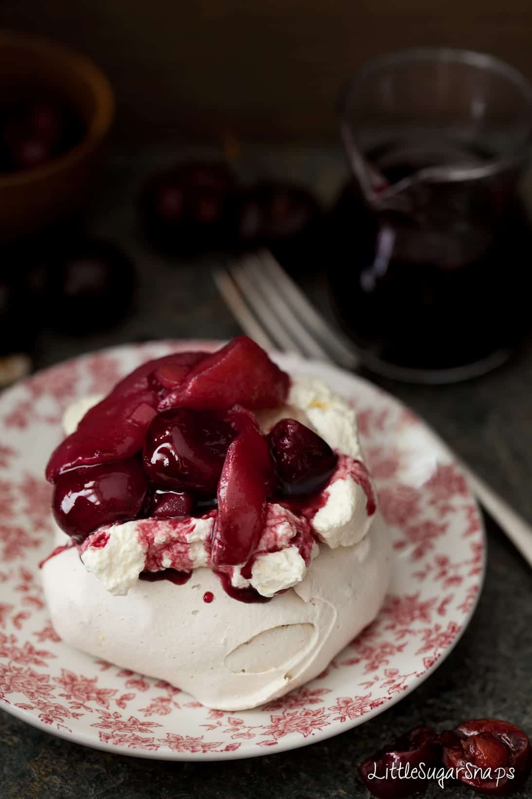Close up of mini pavlova with poached fruit and cream
