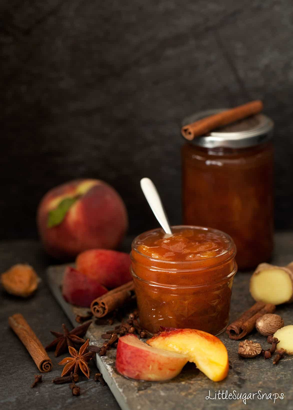 Spiced Peach Jam in a jar with ingredients alongside