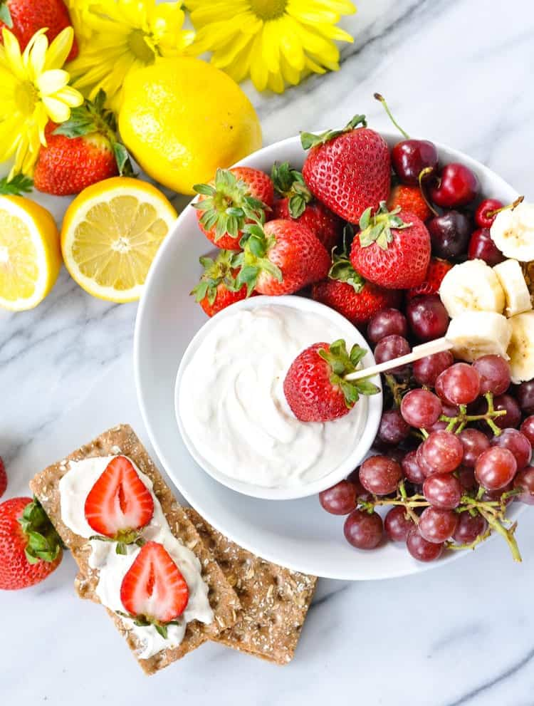 A plate of fruit with sweet dip and crackers.