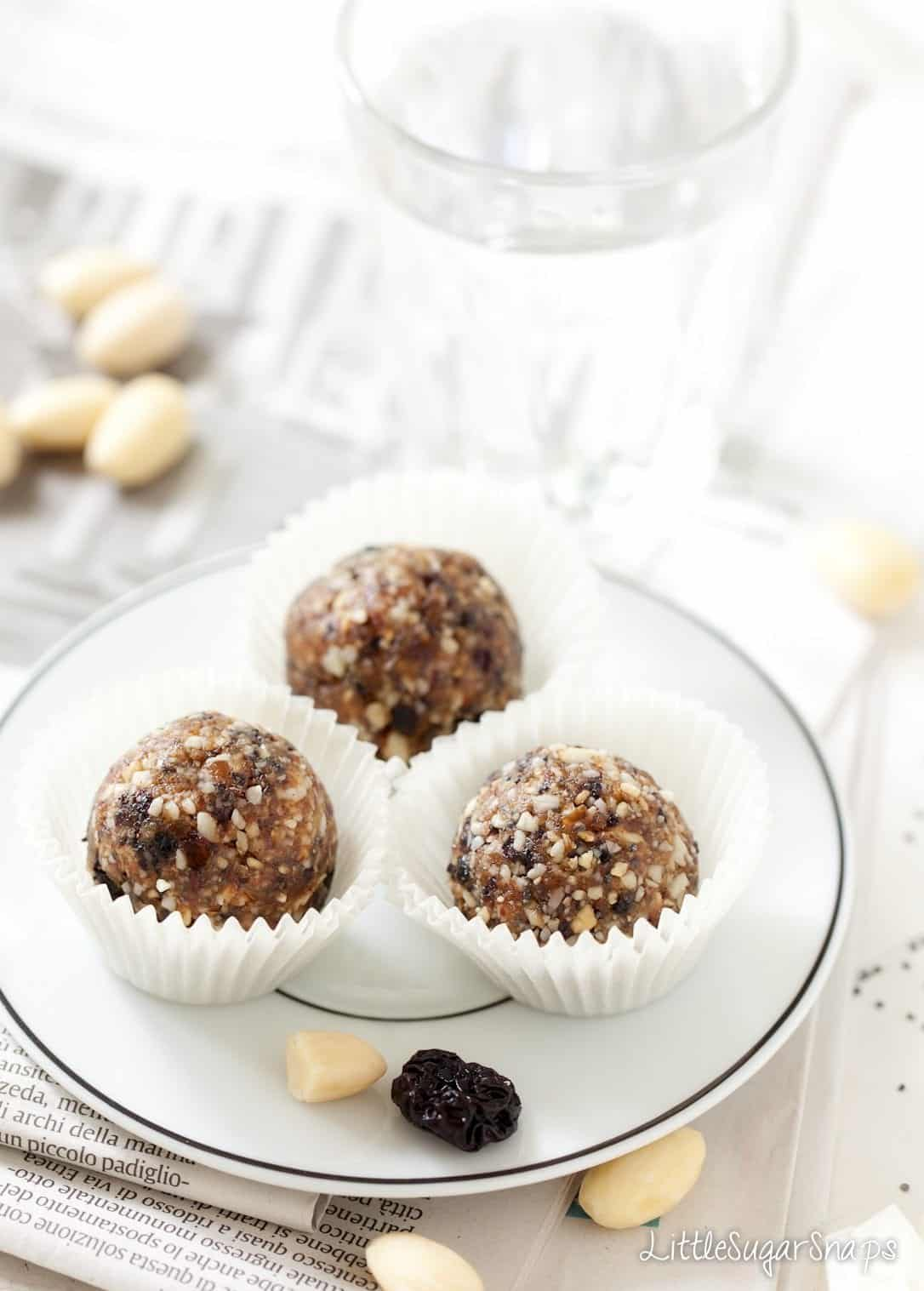 Three Cherry Bakewell Almond Energy Balls on a plate.