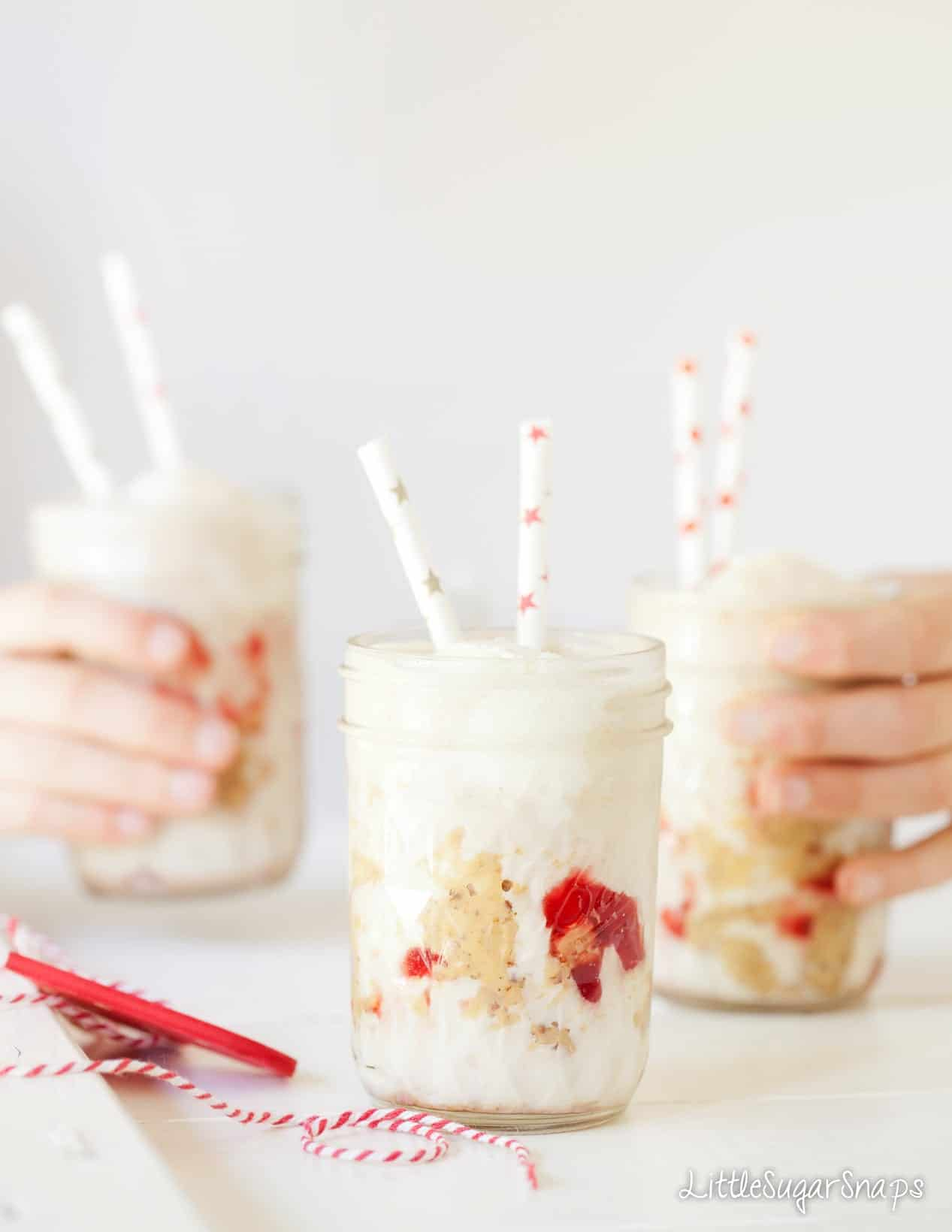 Children taking glasses of Peanut Butter and Jelly Milkshake from a table