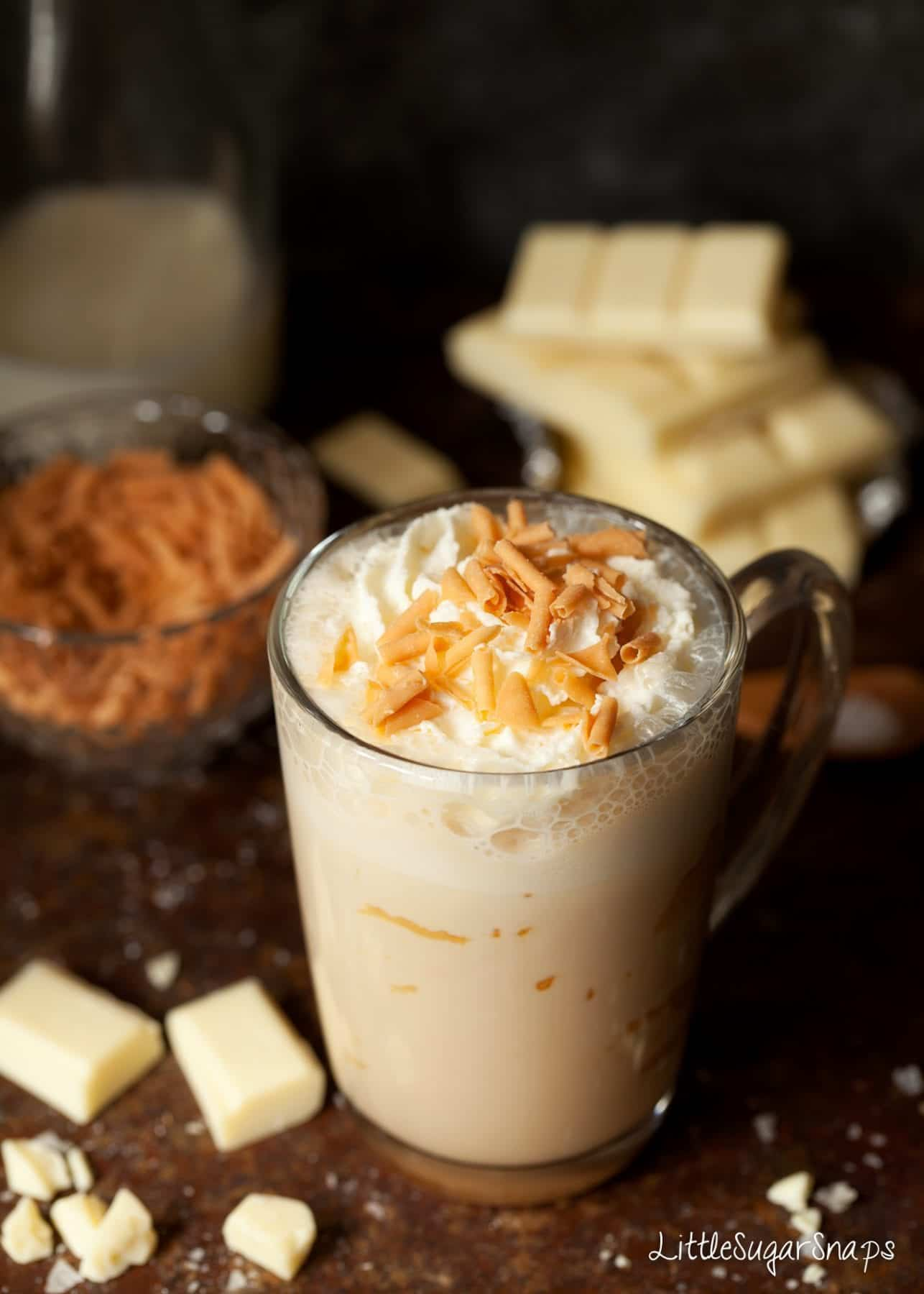 A mug of Caramelised White Hot Chocolate with cream and caramel flakes.