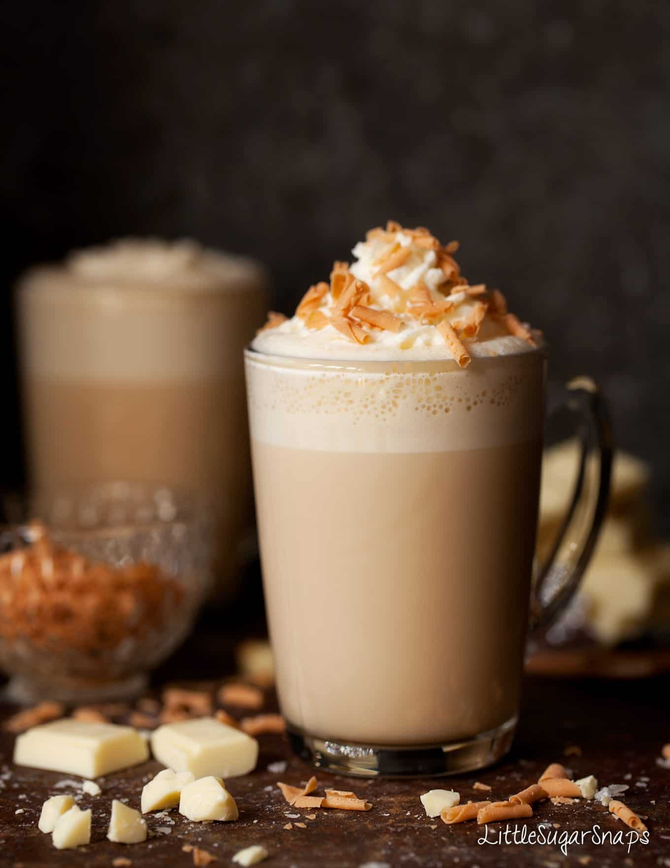 Caramelised White Hot Chocolate in a glass mug with whipped cream and caramel flakes.