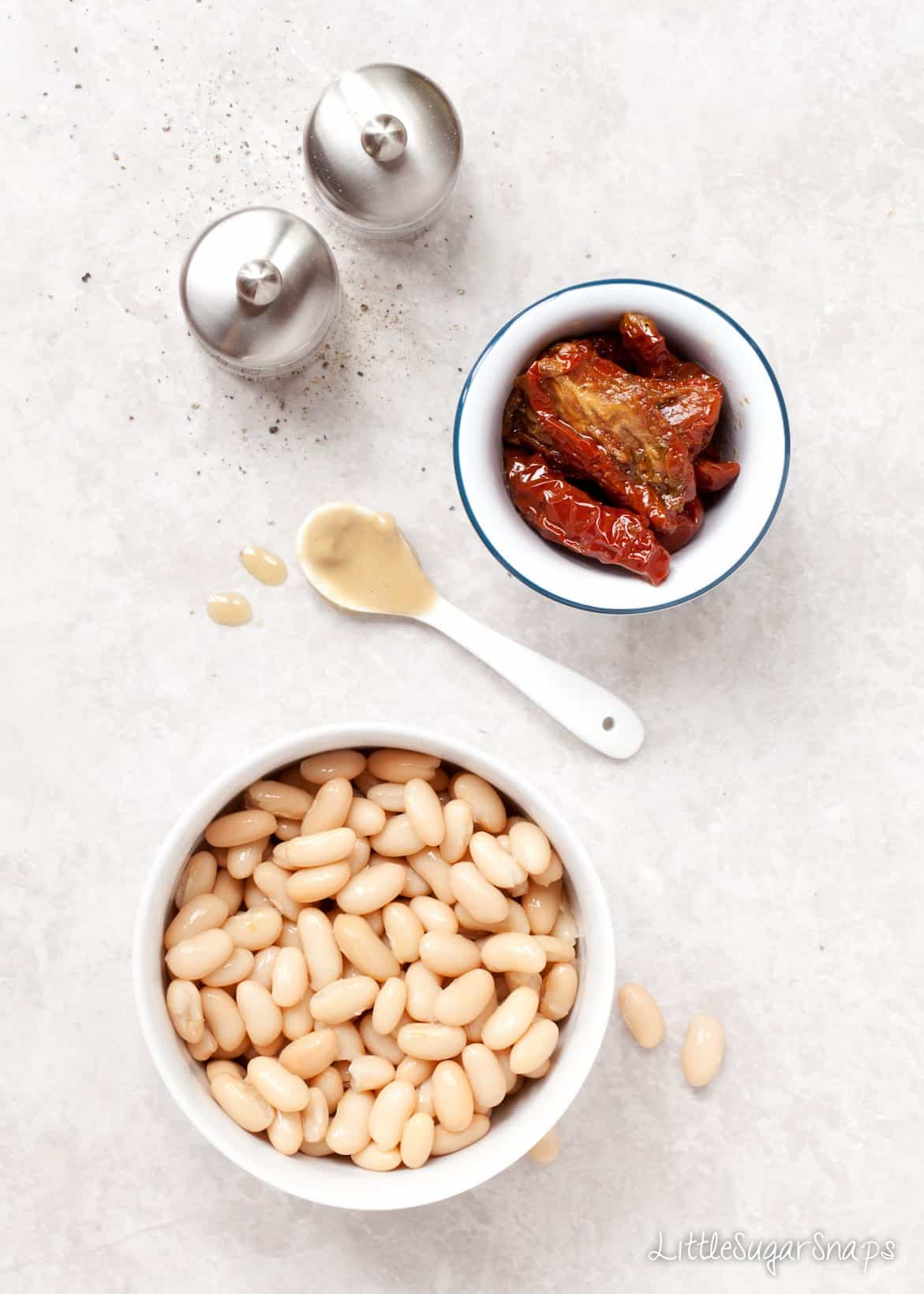 White beans and sundried tomatoes in bowls.