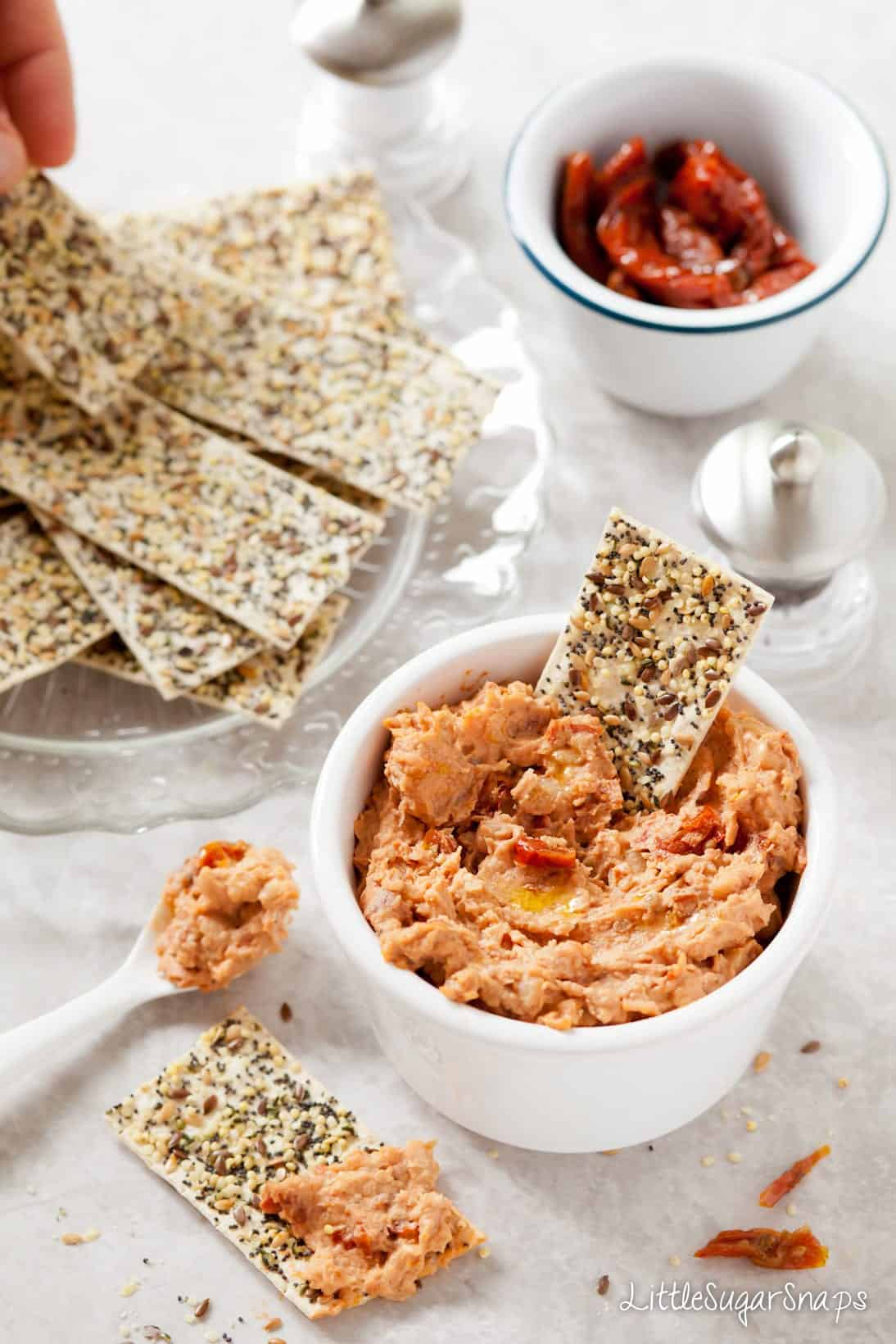 Sundried Tomato White Bean Dip in a bowl with crackers