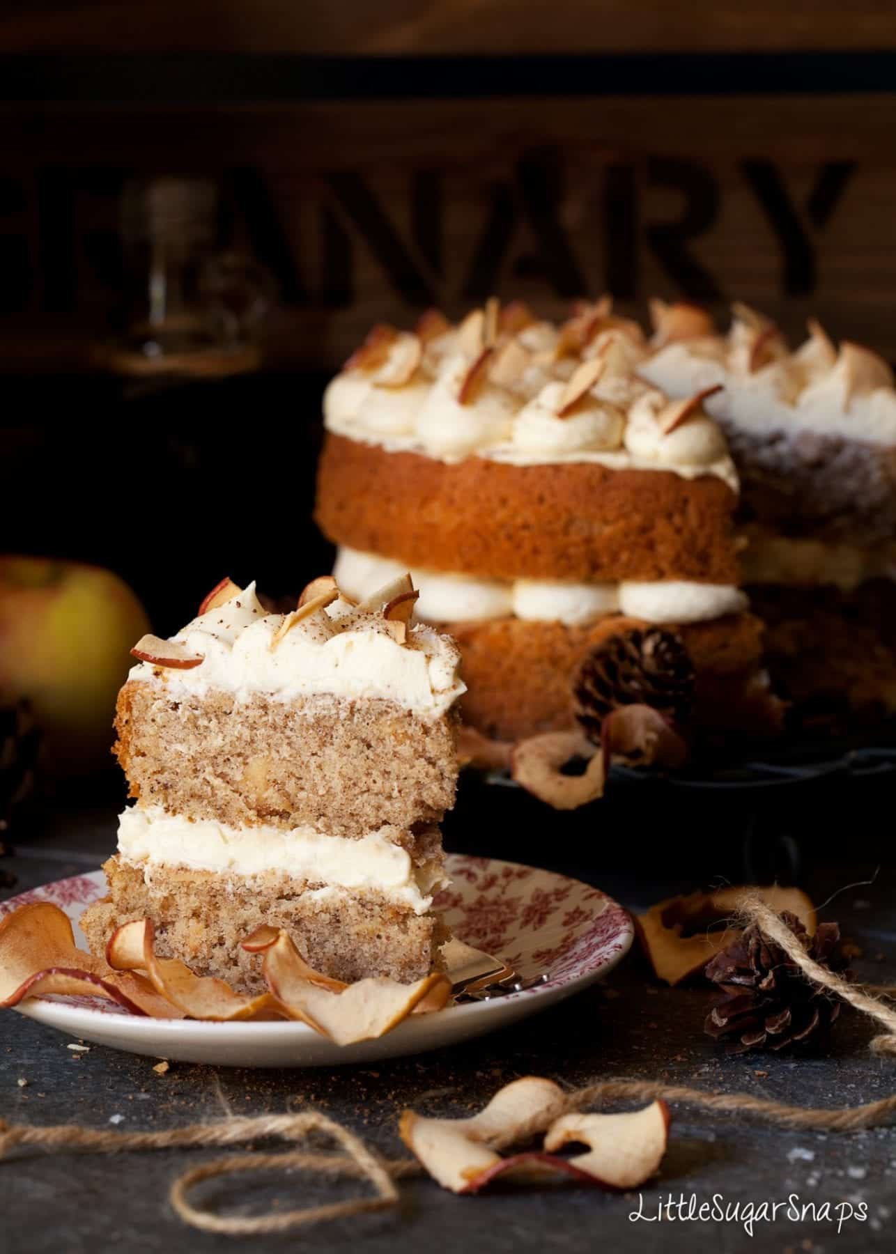 a slice of Apple cinnamon Cake with buttercream and dried apple on a red side plate. Sliced into Layer cake in the background