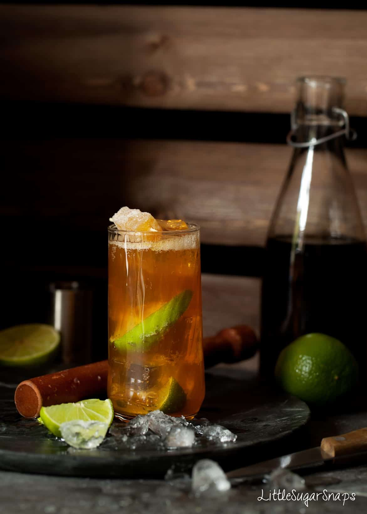 A Dark-n-Stormy cocktail in an ornate glass with ice and fresh lime wedges alongside.