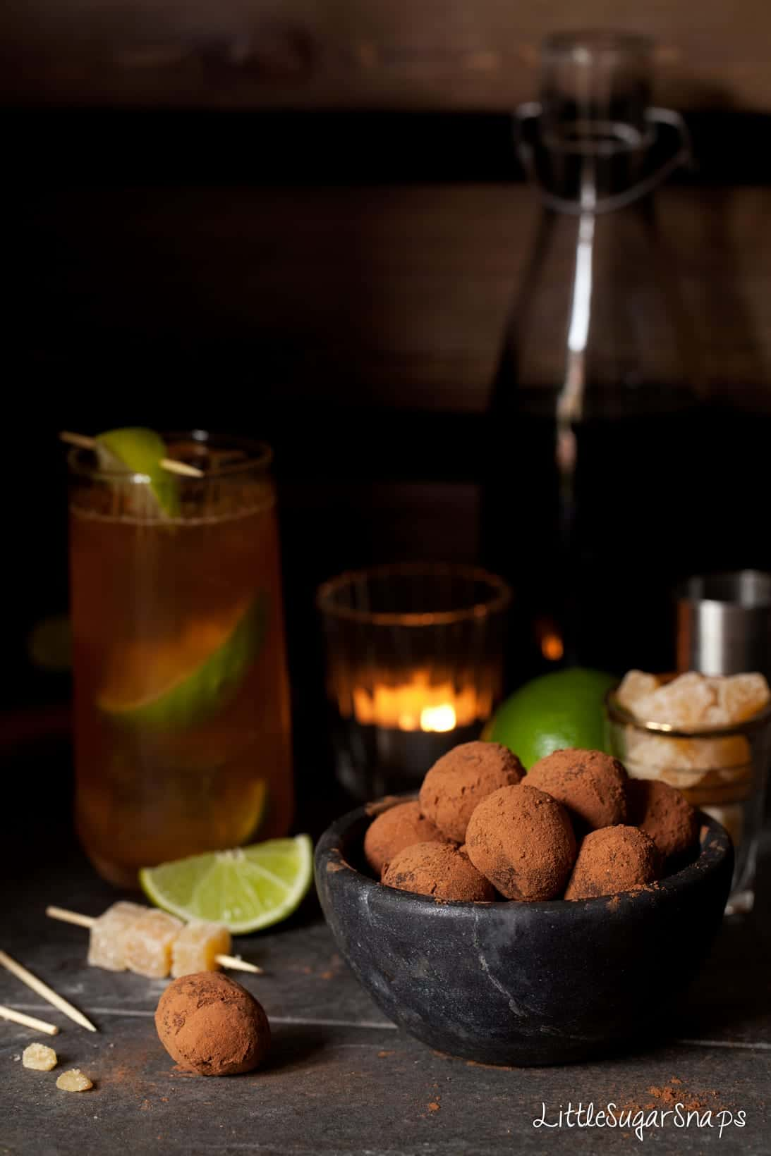 Ginger Truffles in a black bowl with a Dark n Stormy cocktail behind it.