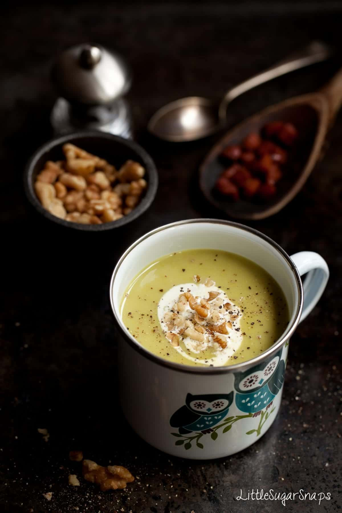 spinach and stilton soup in an owl design enamel mug with cream and walnut garnish on top. bowls of walnuts and chorizo out of focus behind.