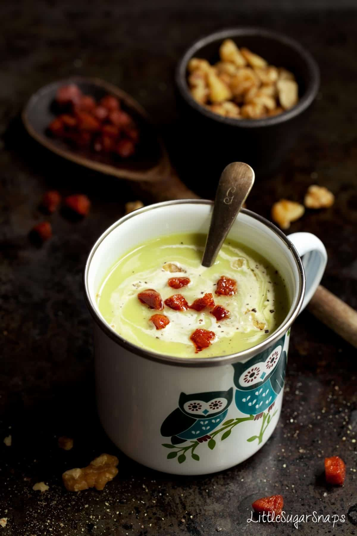 celeriac and Blue Cheese Soup in an enamel bug with an owl on it. shot on a dark background and garnished with cream & fried chorizo