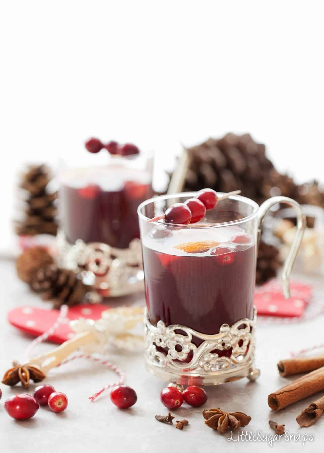 Mulled Grape Juice in a vintage glass mug with fresh cranberry garnish.
