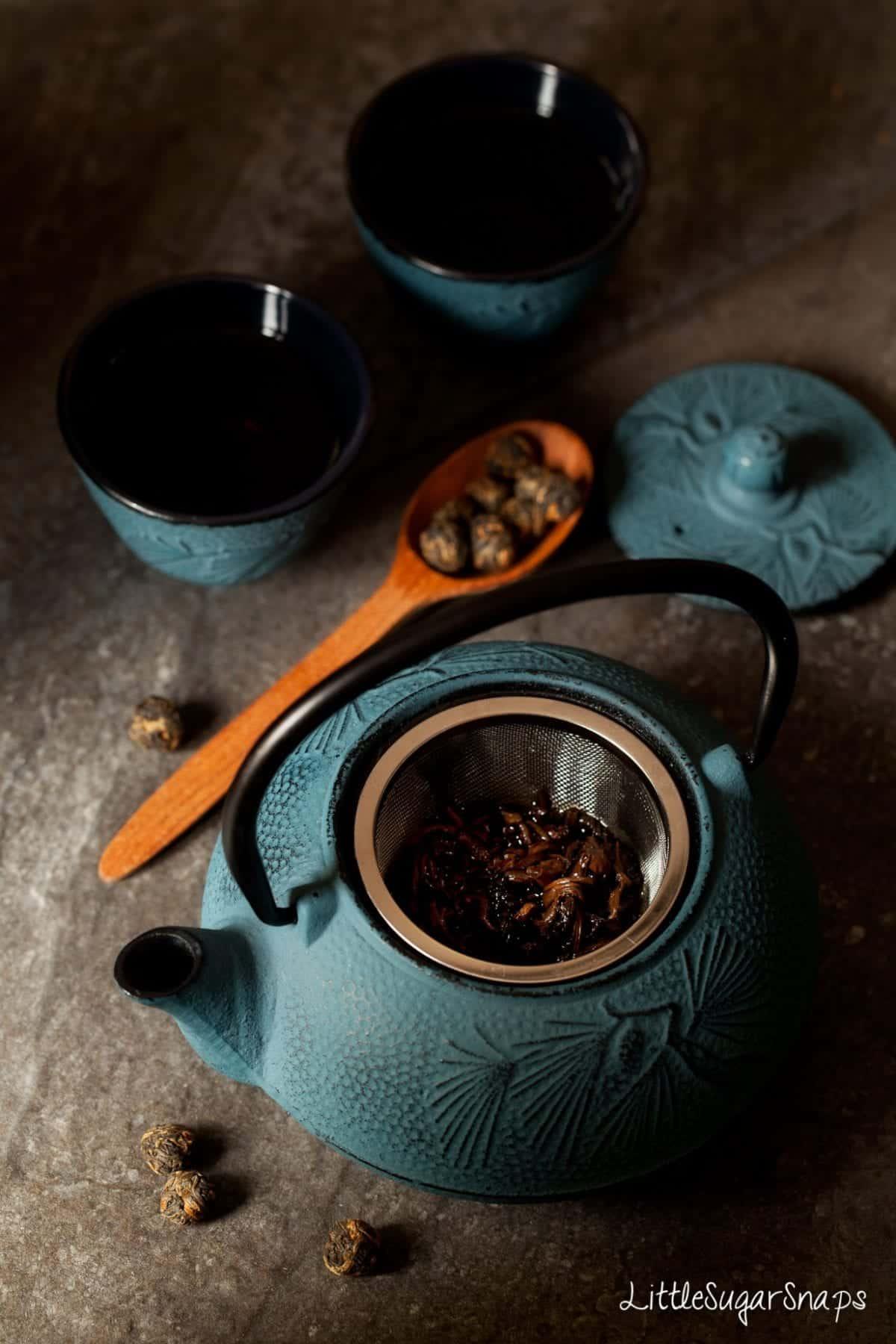 Tea brewing in a blue cast iron teapot.