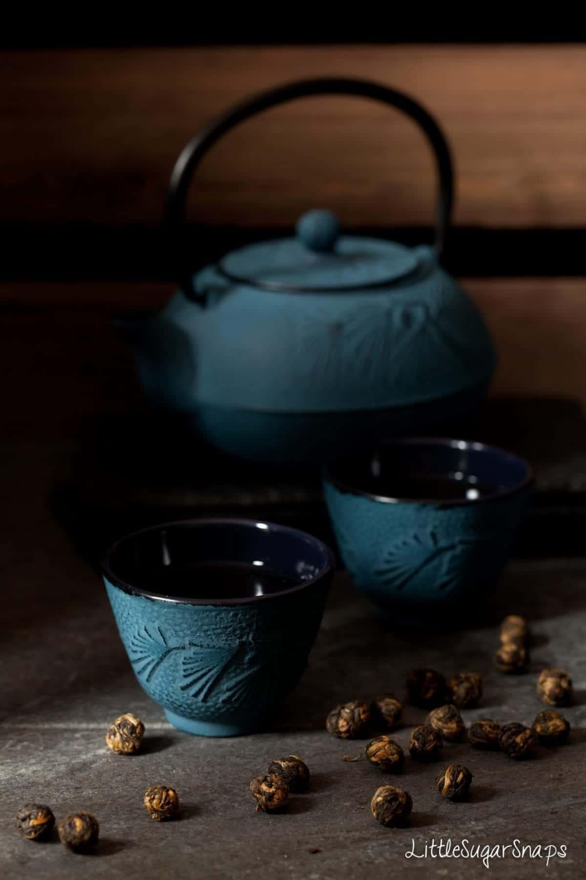 Cast iron tea cups and teapot with tea pearls alongside.