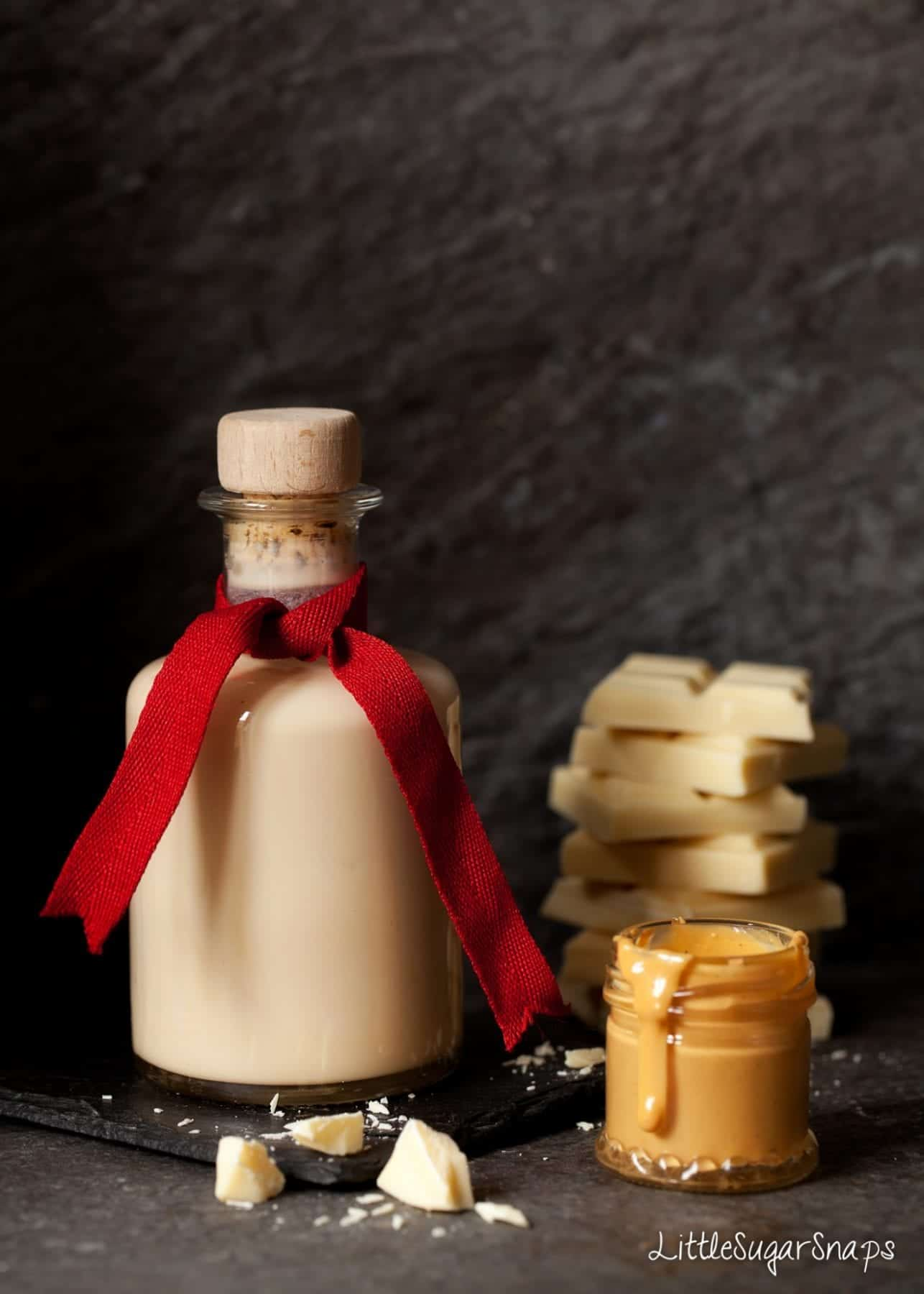 a bottle of homemade cream liqueur with ingredients at the side