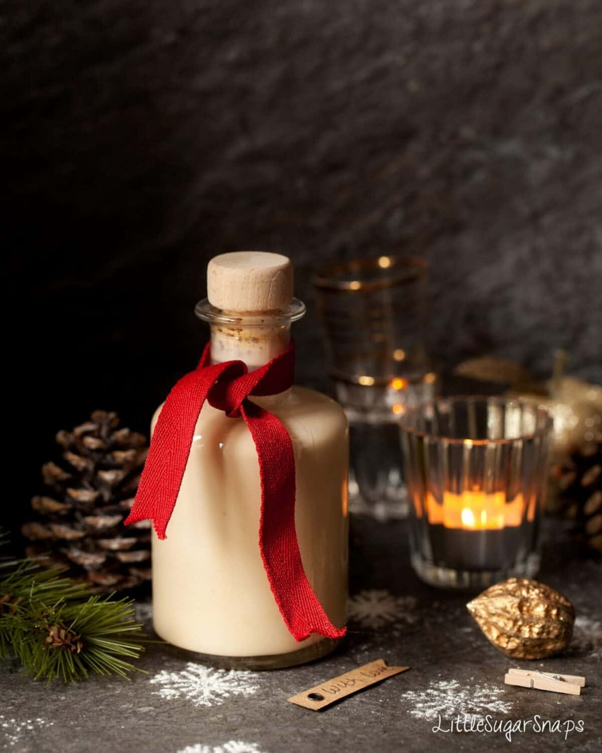 White Chocolate Liqueur in a bottle tied with a red ribbon, candles, pine cones and snowflakes nearby
