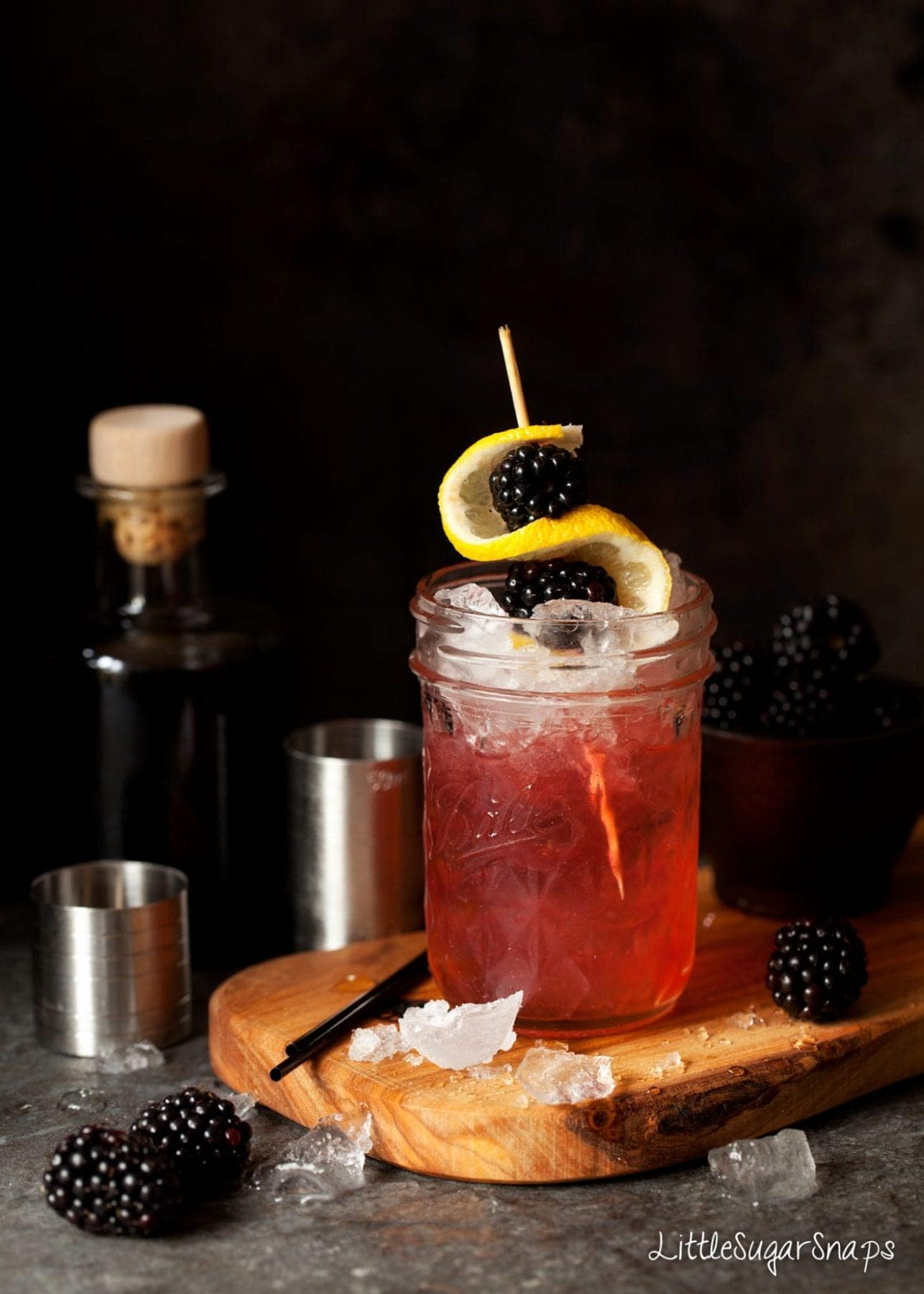 A Bramble cocktail garnished with ice, lemon and blackberries.