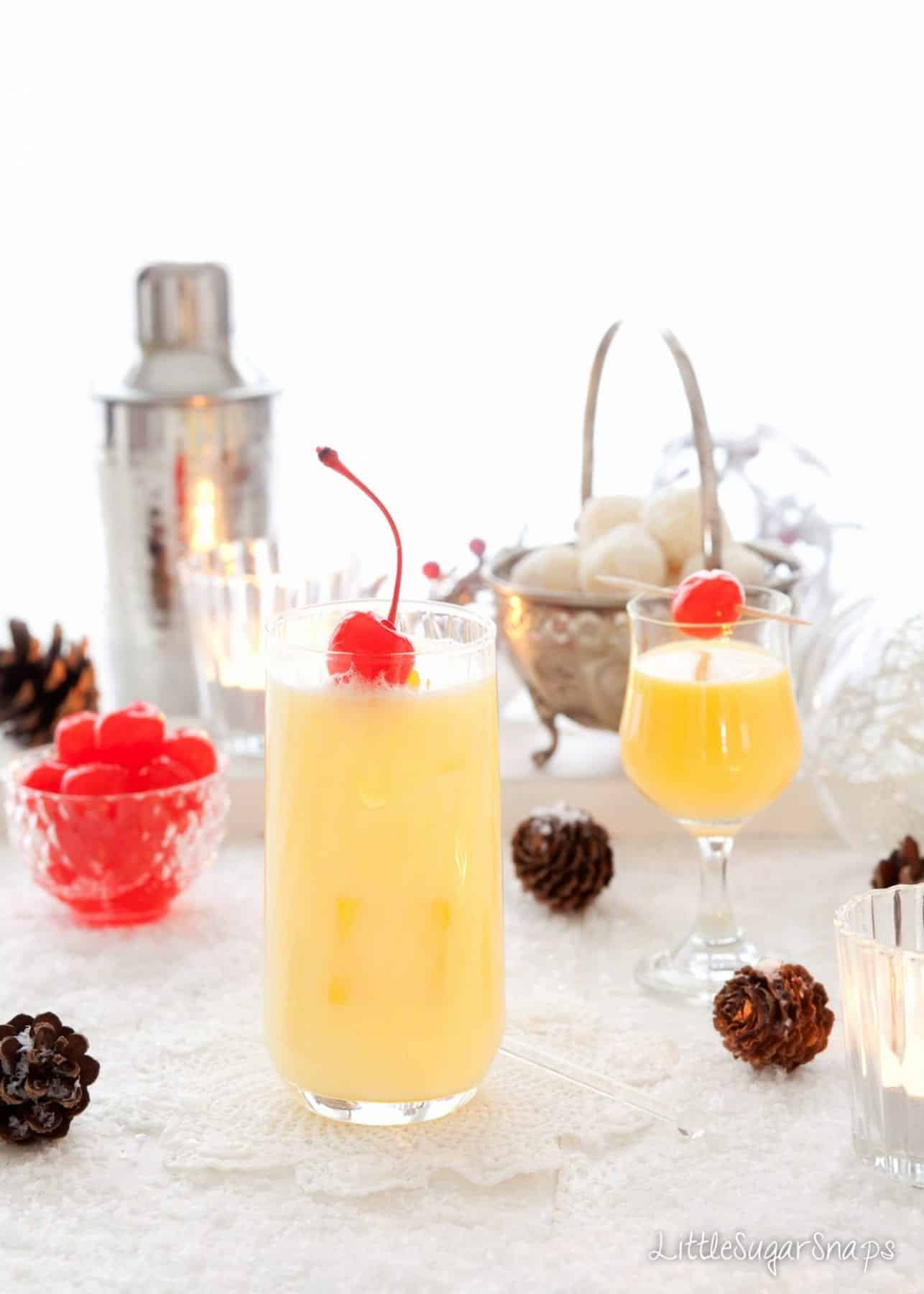 A classic snowball cocktail and a glass of Advocaat. Both are garnished with cocktail cherries.