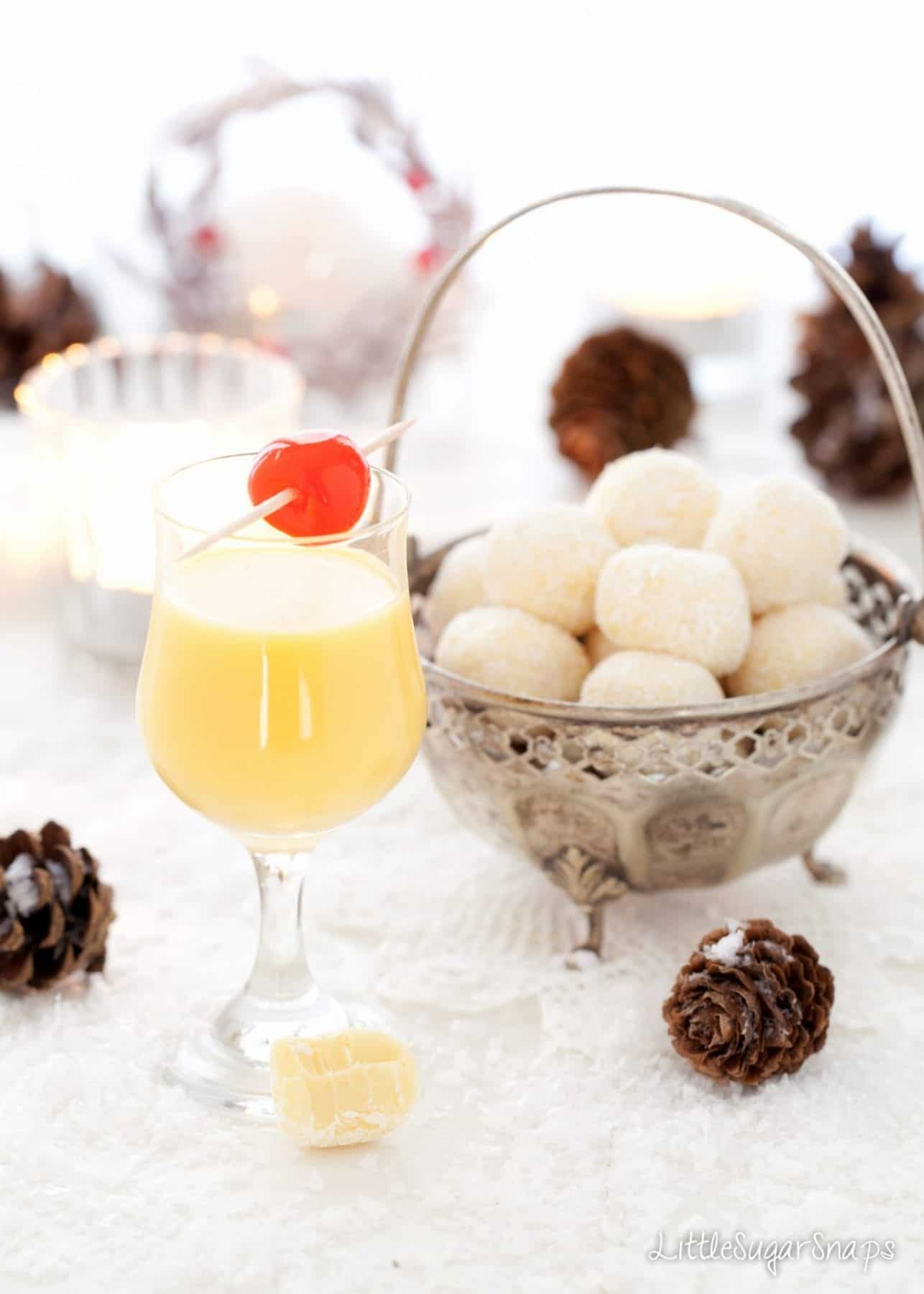A glass of advocaat next to a bowl of Snowball Truffles