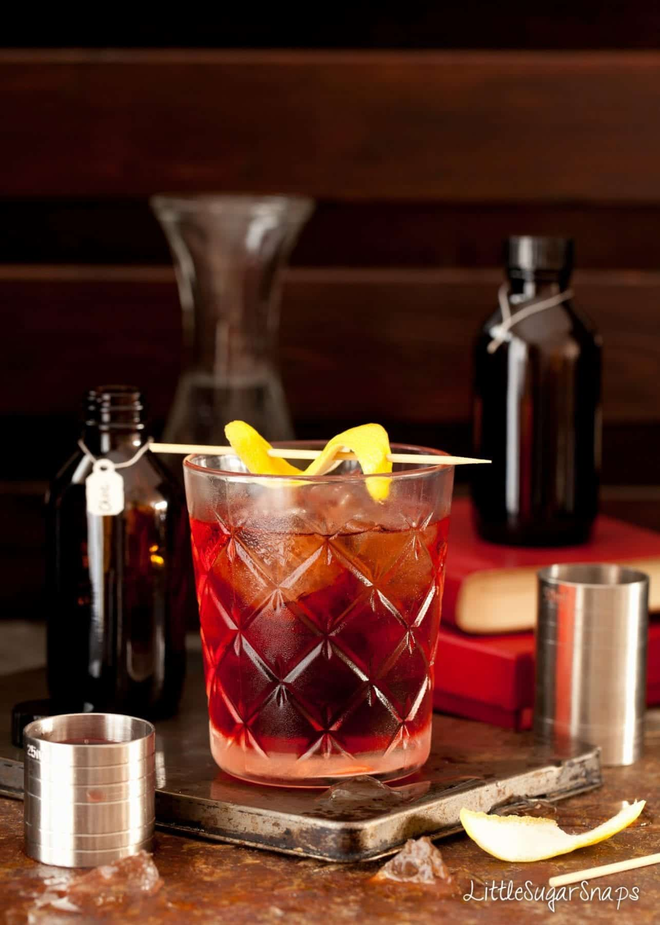 A classic negroni cocktail garnished with fresh lemon.