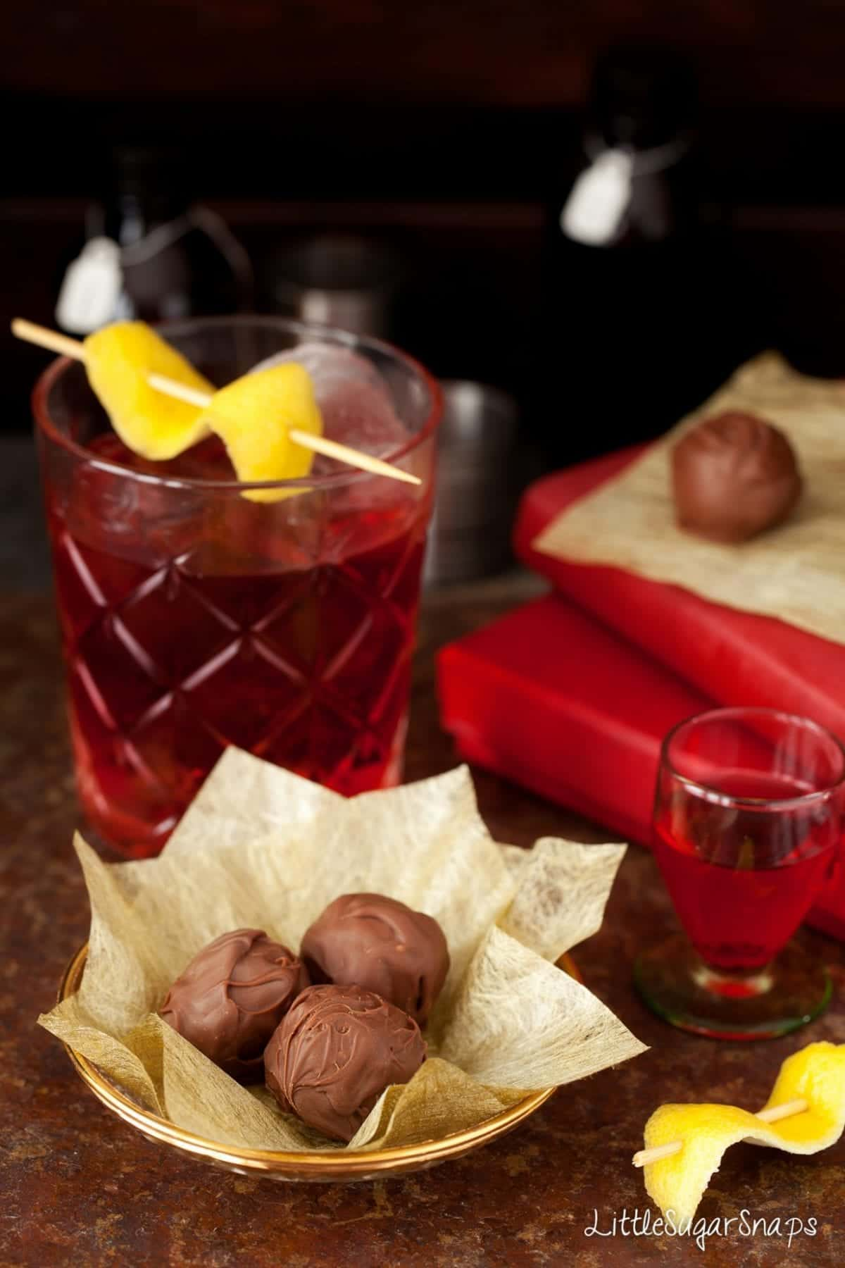 Negroni Truffles in front of a Negroni cocktail.