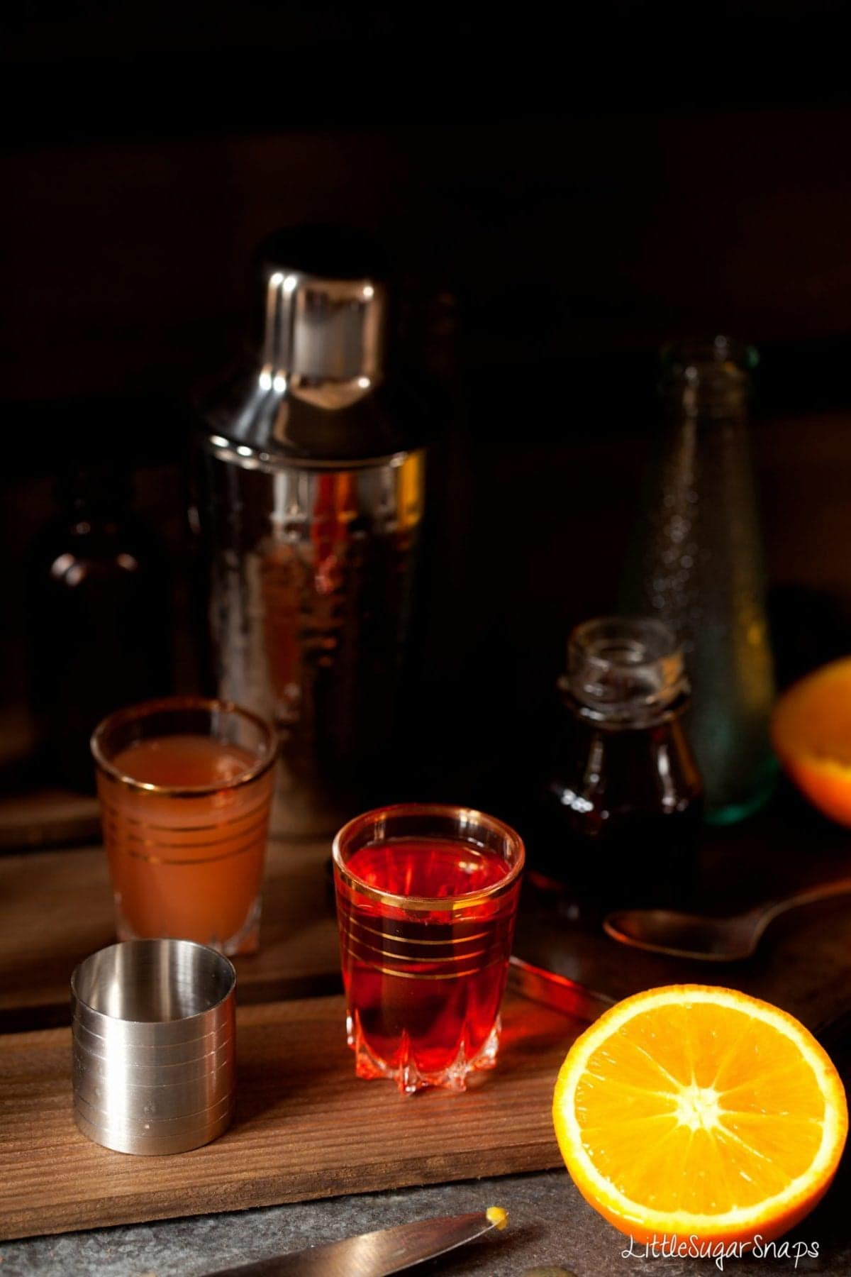 Shot glass containing Aperol  with grapefruit juice and fresh orange alongside.