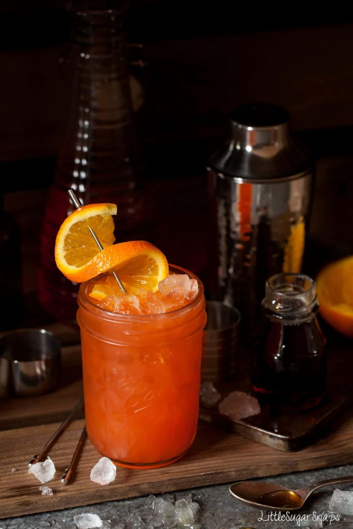 A tequila and Aperol cocktail garnished with a twist of orange.
