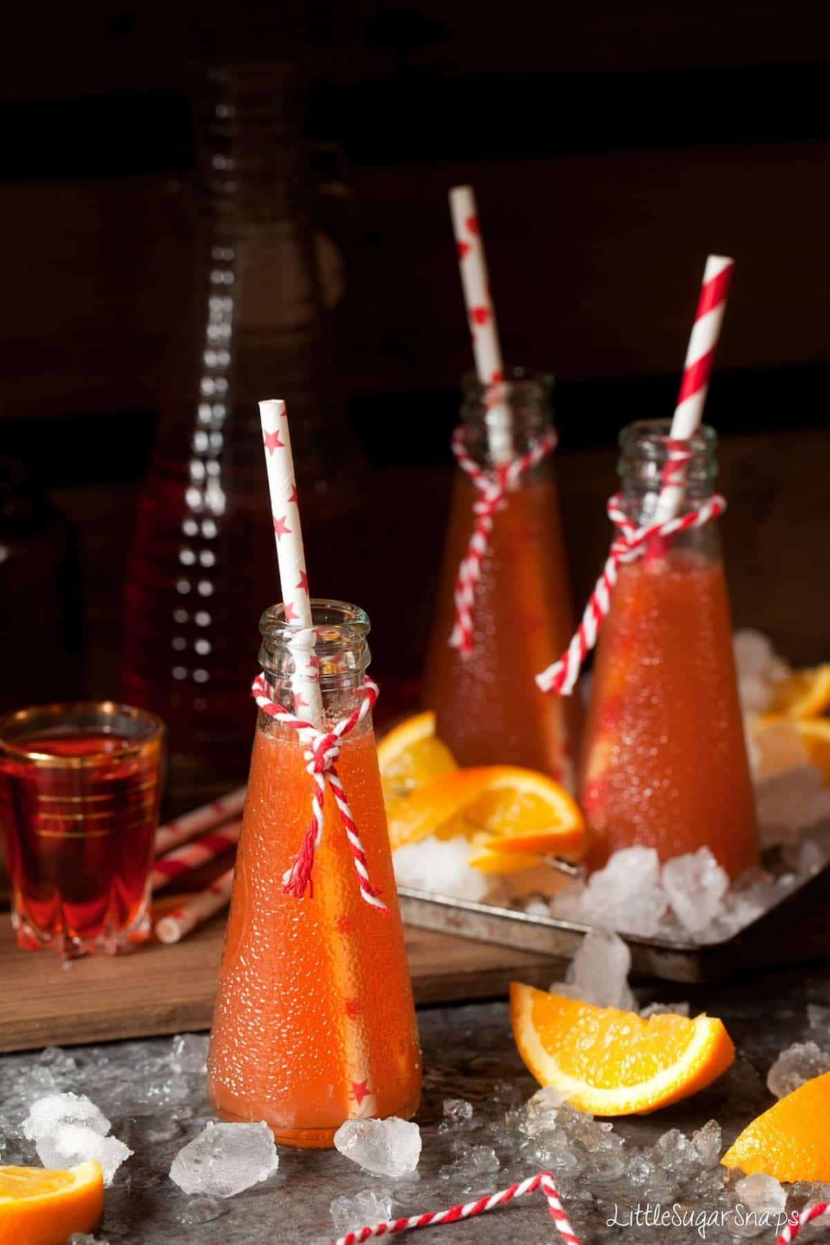 Bottles of orange cocktail with orange wedges and aperol alongside.