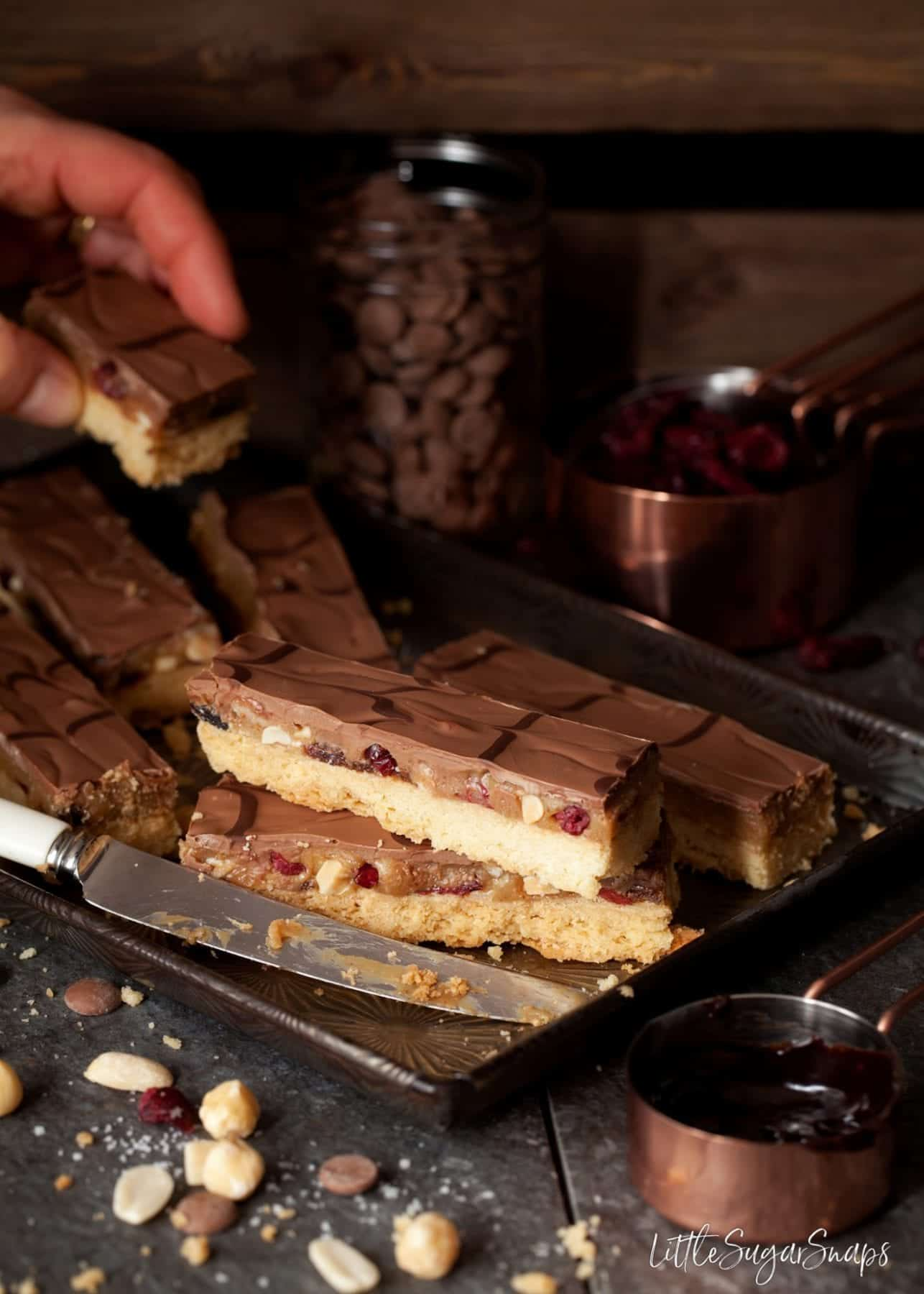 millionaire's shortbread bars on a vintage baking tray. Person taking a slice