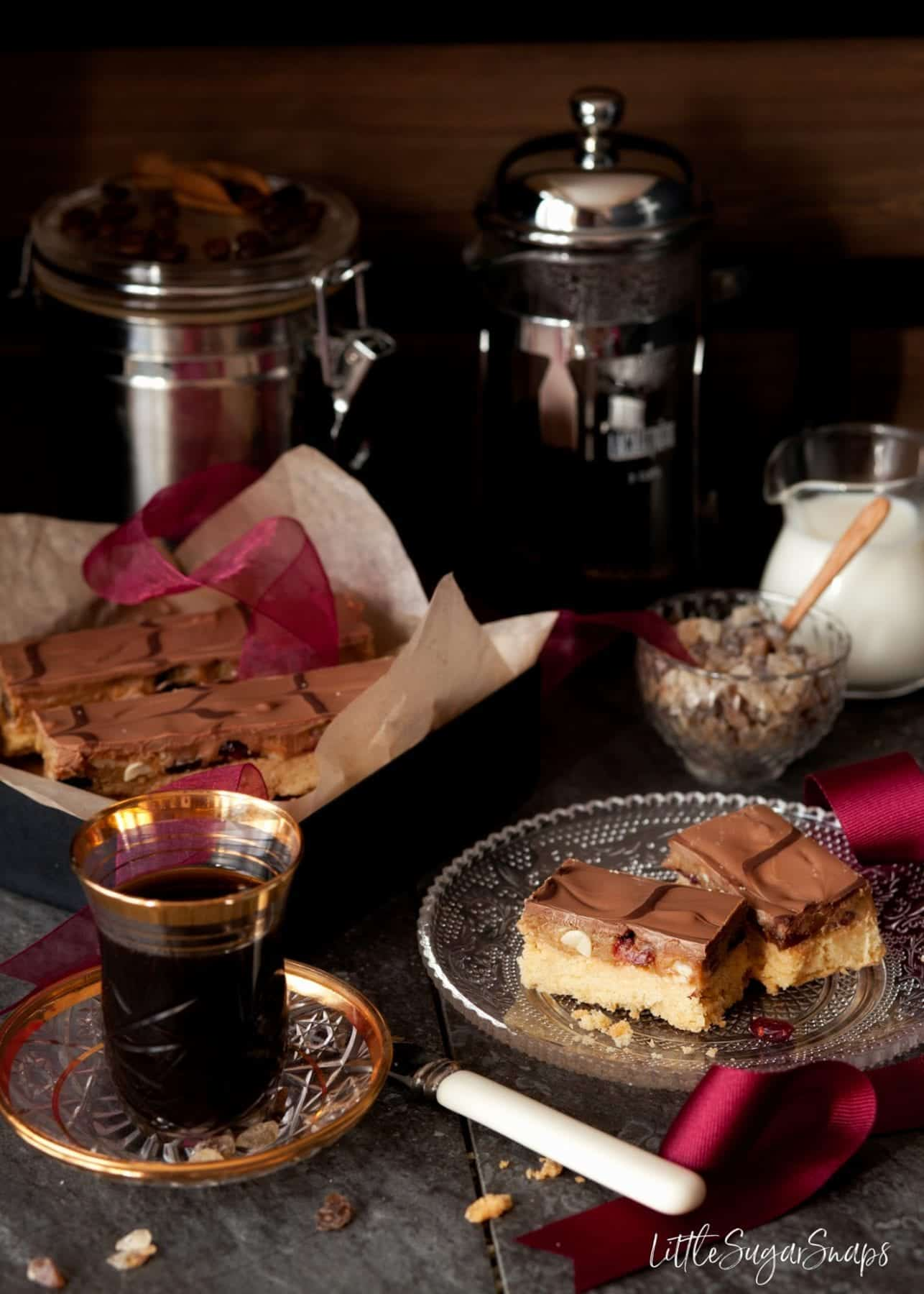 Caramel Shortbread with fried cranberries and nuts. Cafetiere of coffee in the shot with cream and sugar