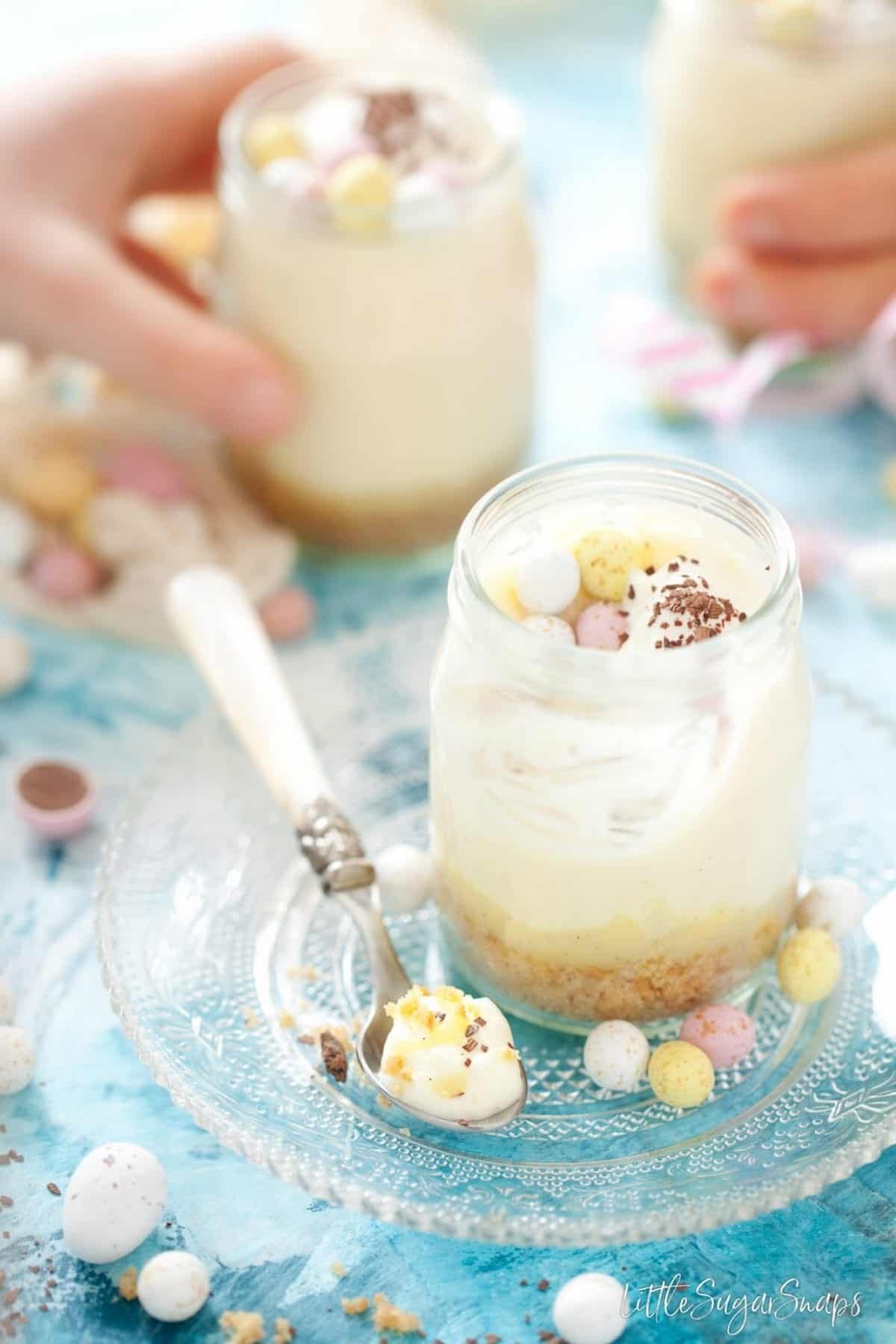 Easy easter dessert recipe with white chocolate, lemon curd, crushed biscuits and mini eggs. Dessert served in glass pots, once is part eaten, hands are taking others away