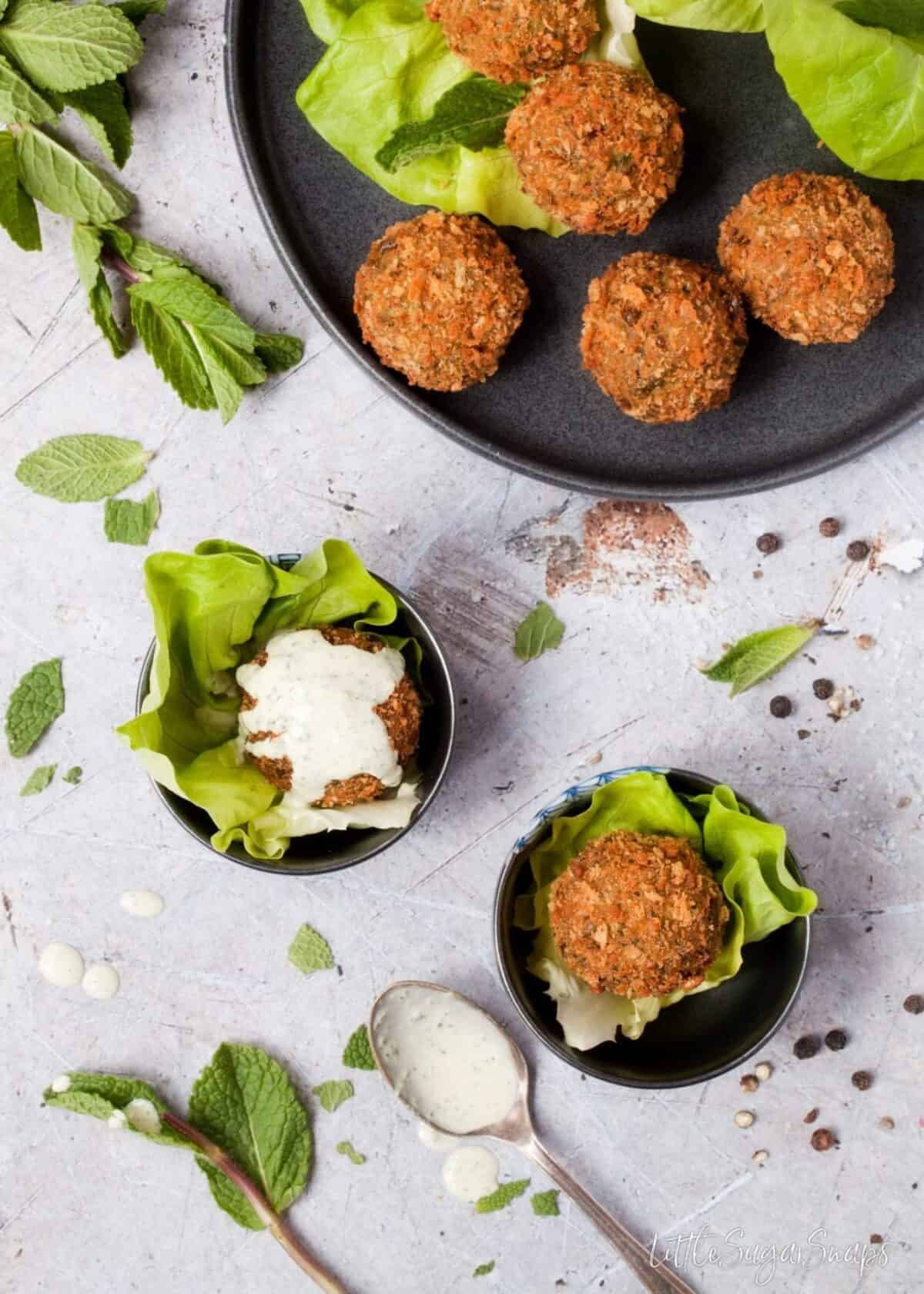 Mint Pea Falafel with mint tahini sauce served on top.