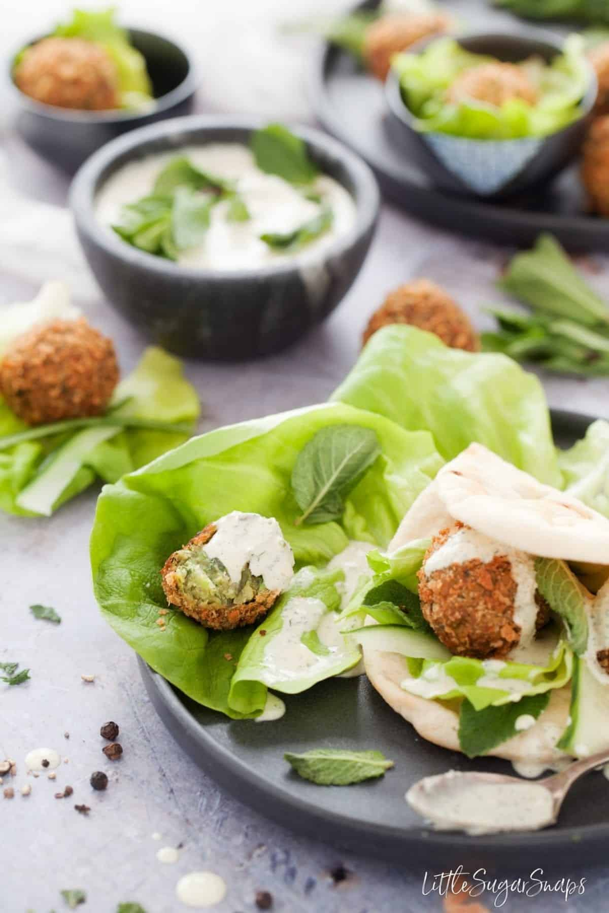 Mint Pea Falafel with lettuce, flatbread and dressing.