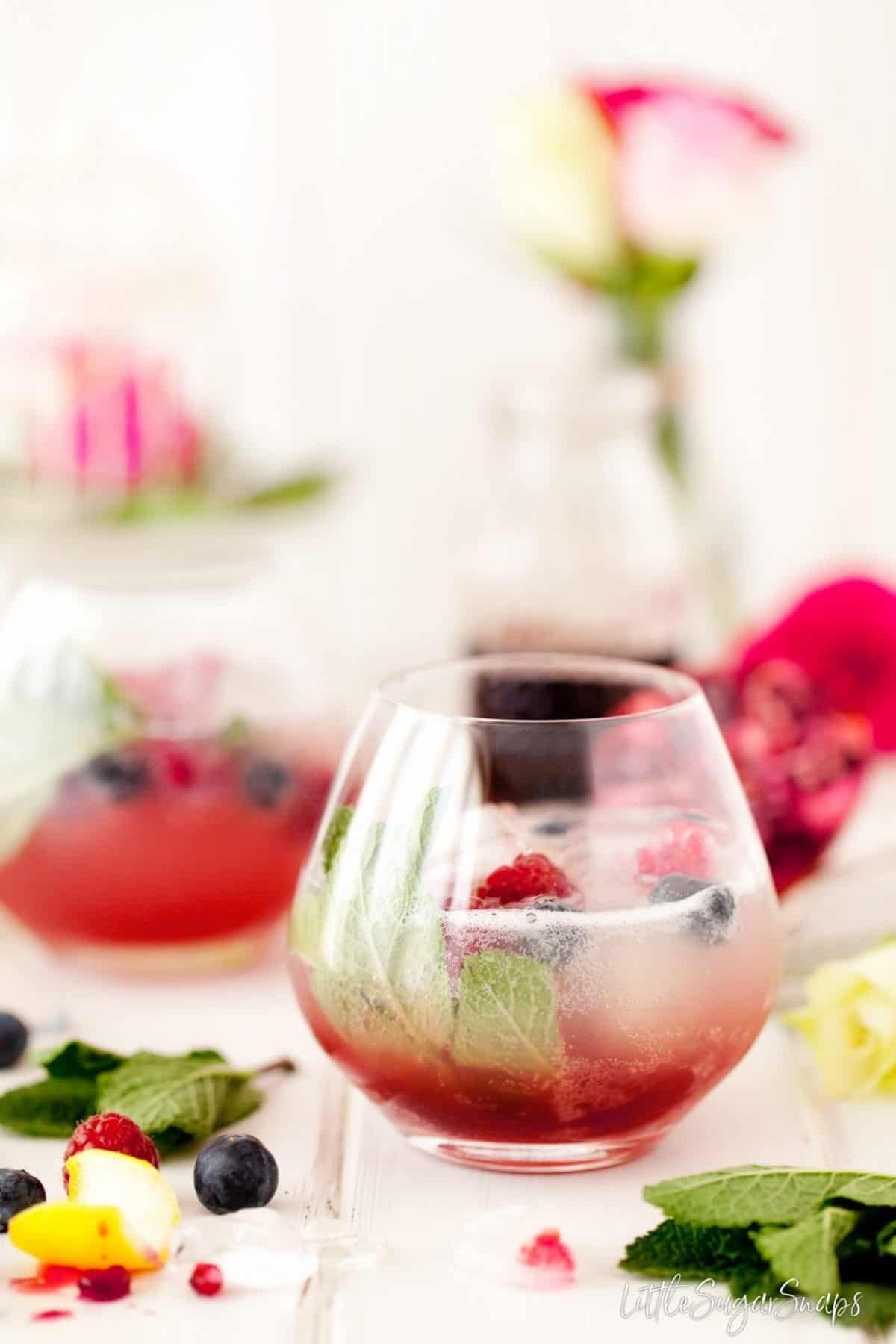 A fruity drink made with grenadine and garnished with mint and berries.