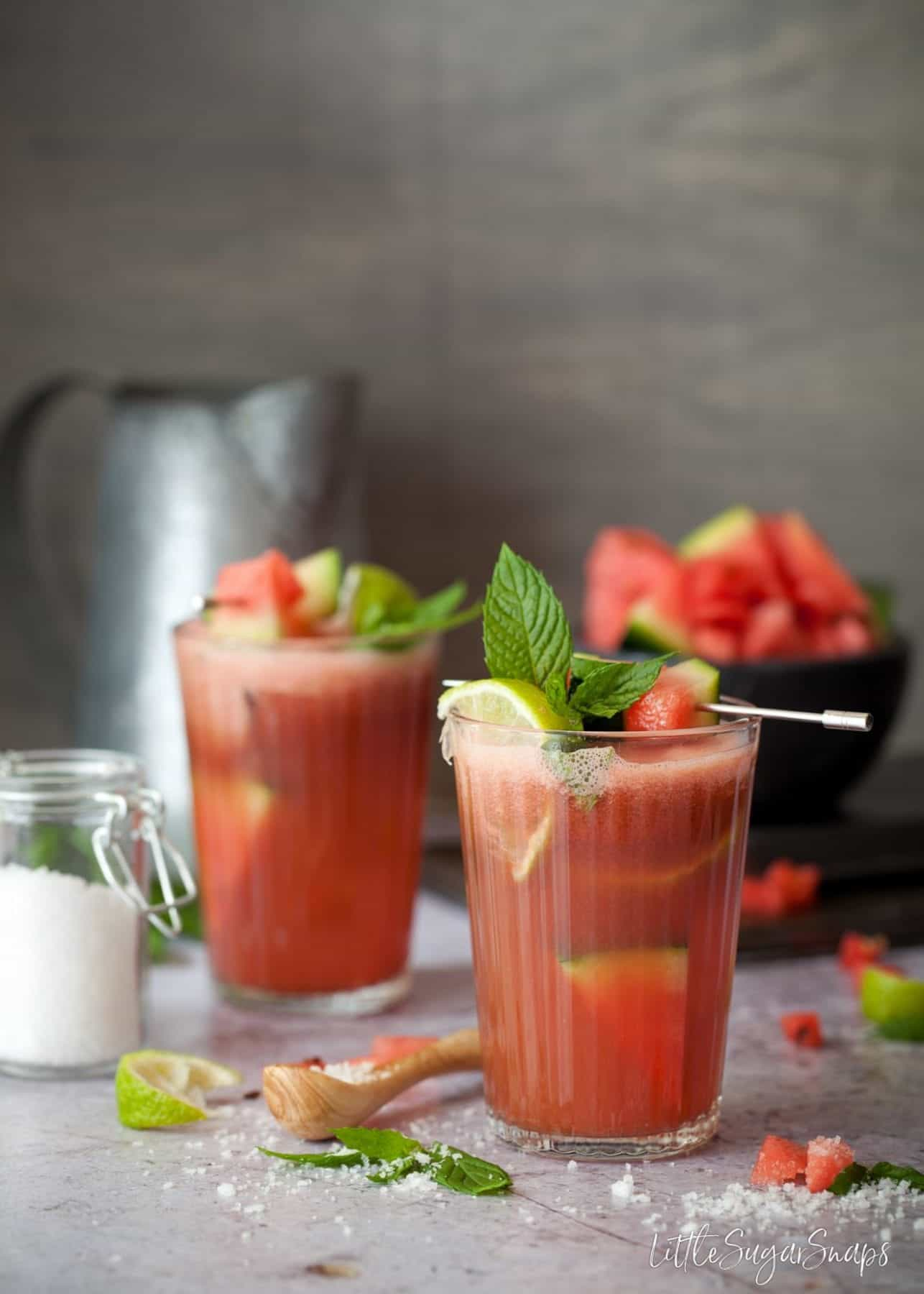 Two glasses of watermelon juice garnished with lime, mint and fruit.