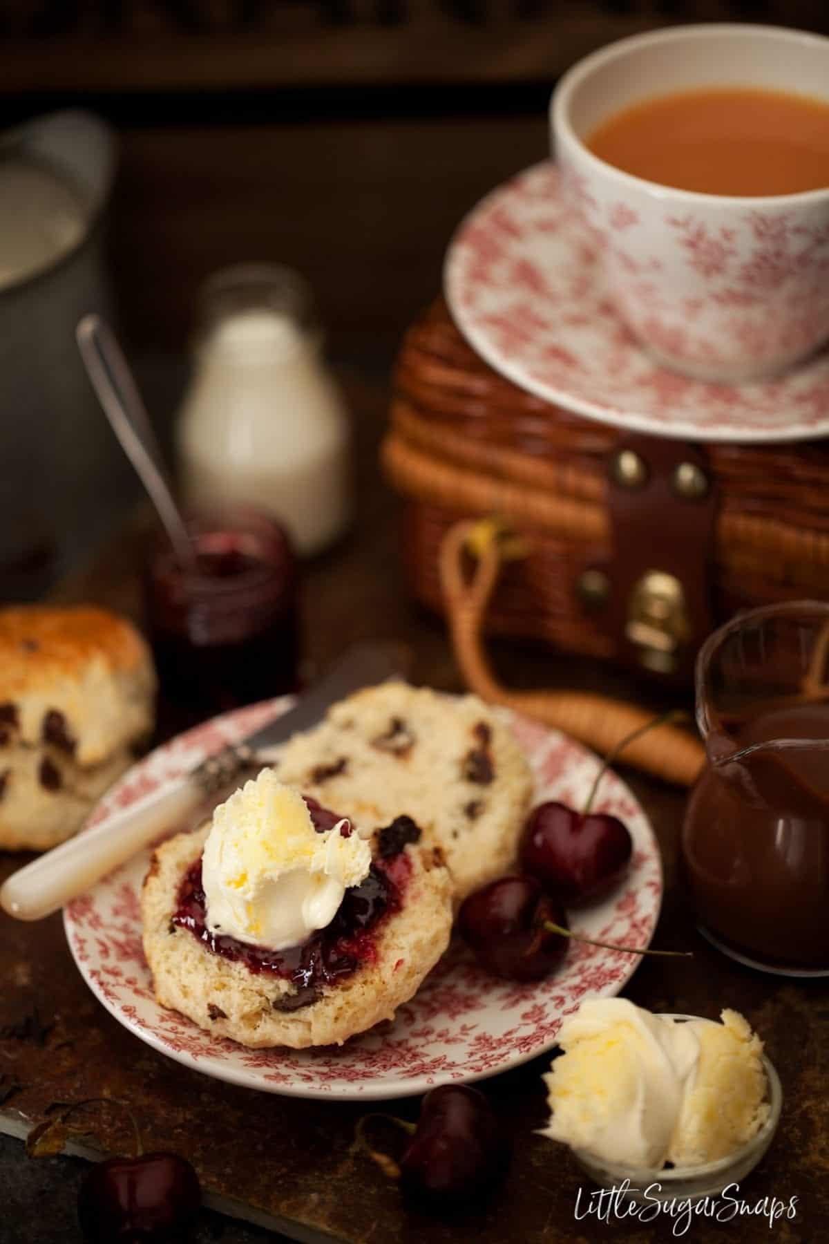 Chocolate chip scone with jam and clotted cream as part of a cream tea.