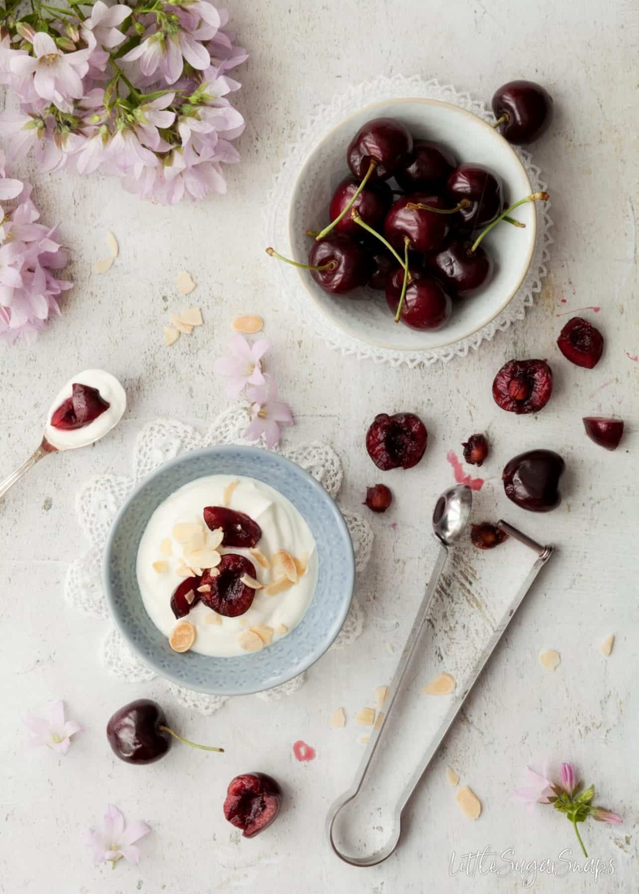 Fresh cherries with a bowl of yoghurt.