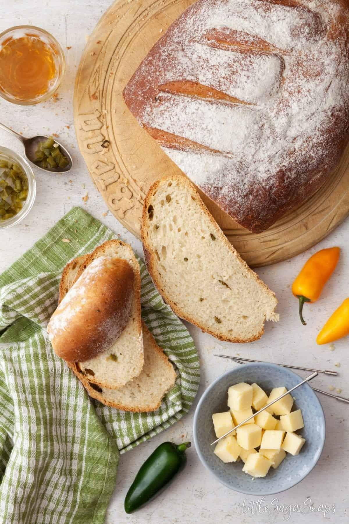 Part sliced loaf of jalapeño cheddar bread with ingredients alongside
