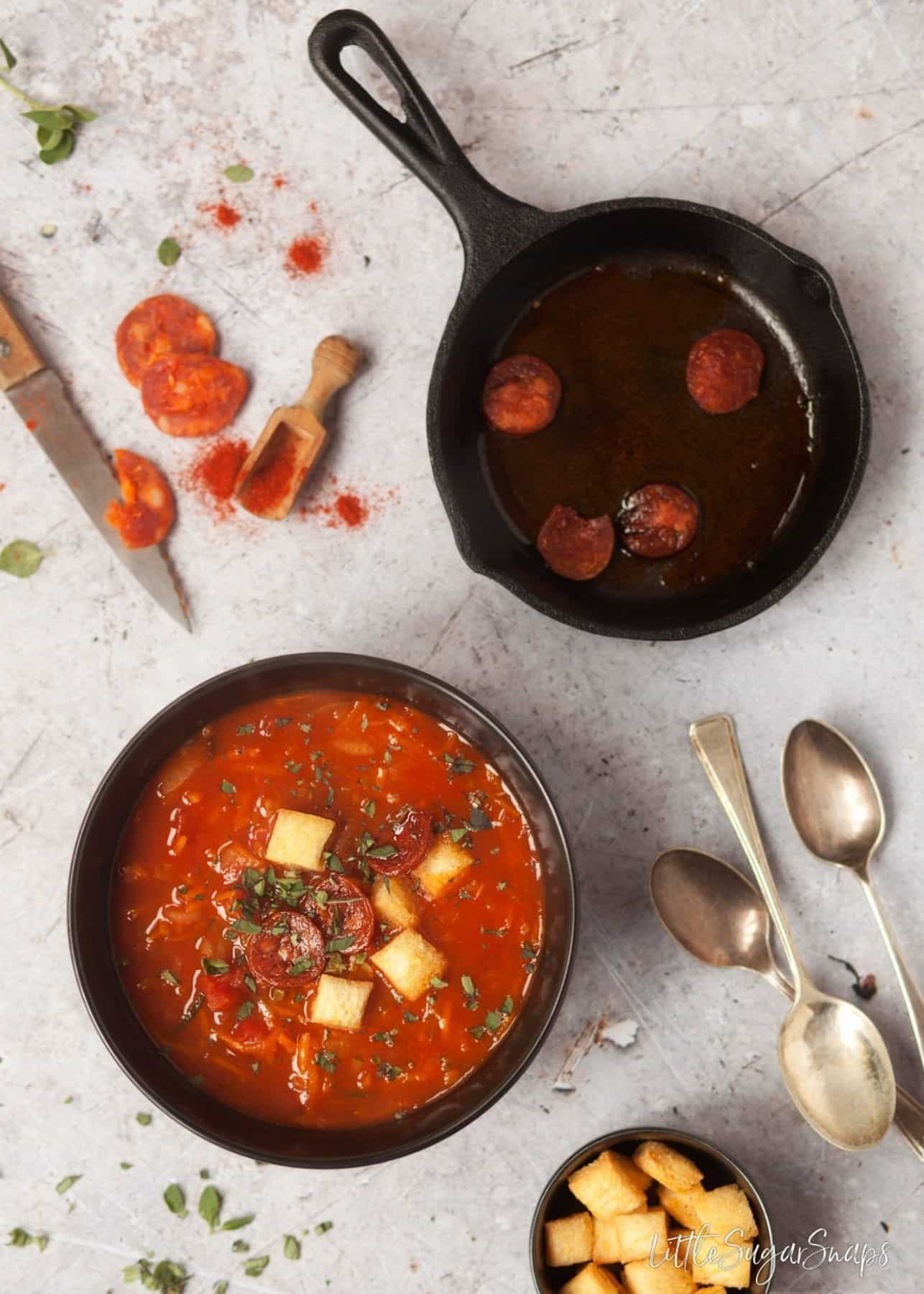 Hearty Paprika Soup with Carrot and Zucchini garnished with fried chorizo slices
