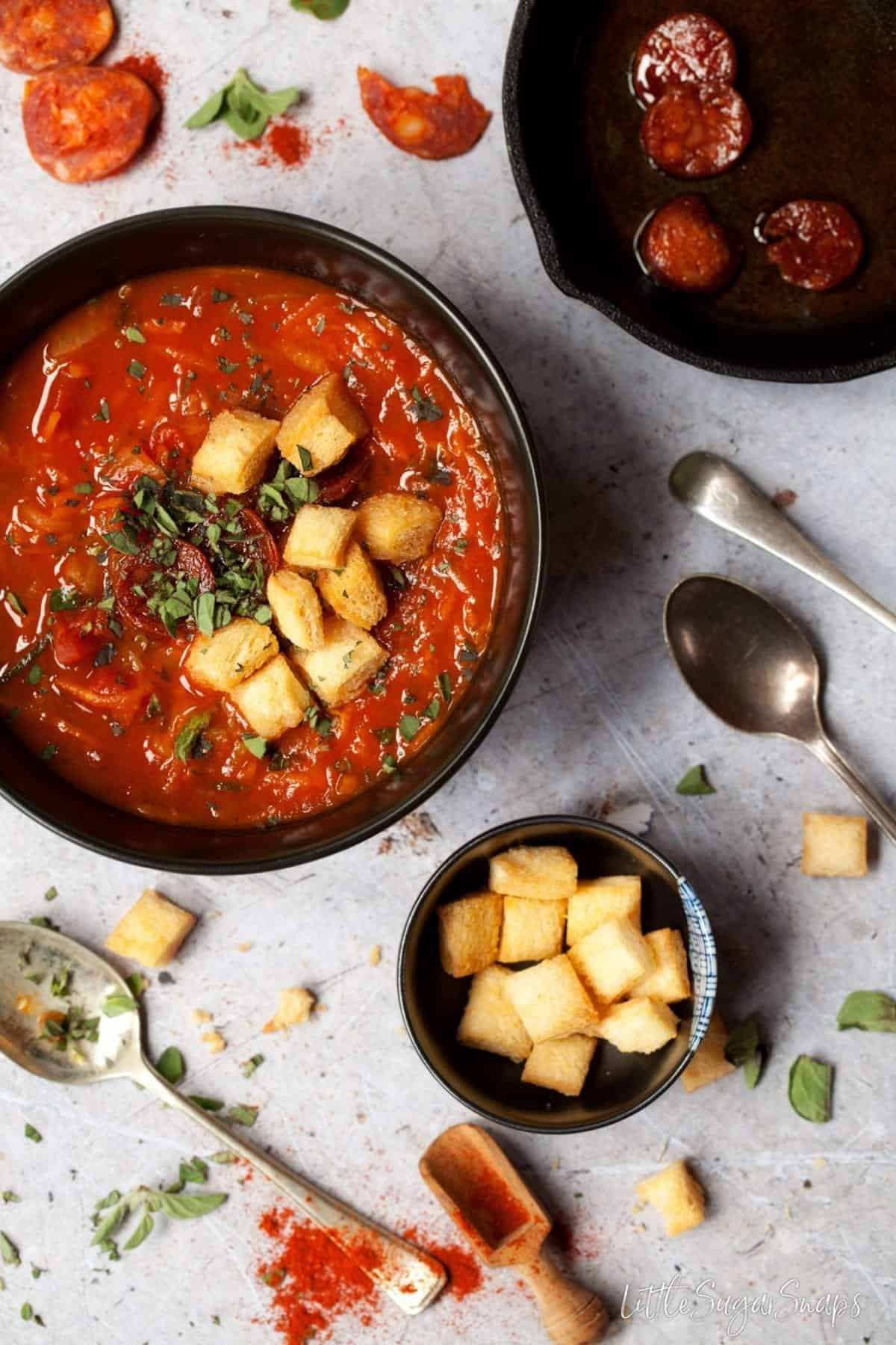 Tomato, Carrot and courgette soup in a bowl with croutons and fresh oregano