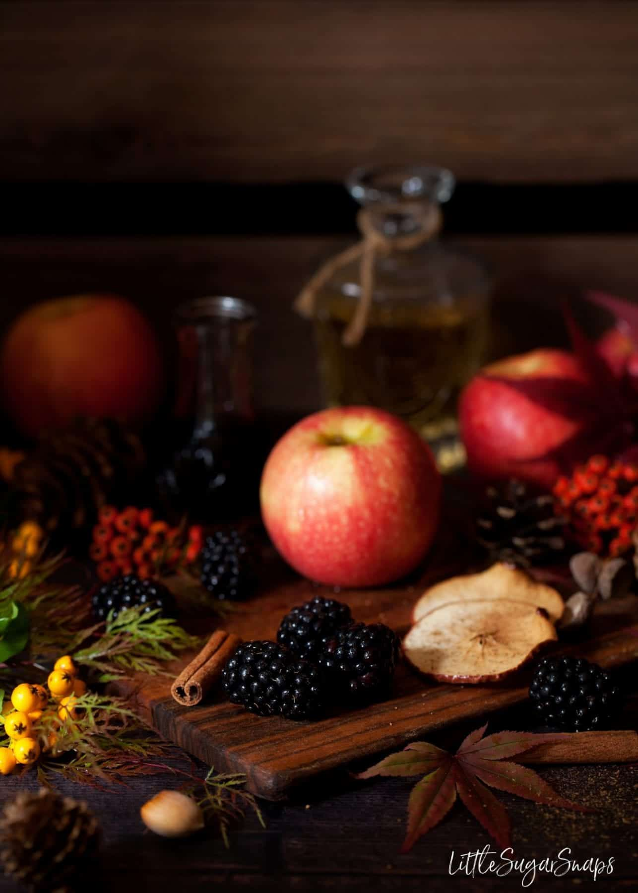 Autumn fruits on a wooden board with seasonal foliage alongside.