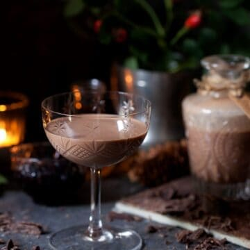 Chocolate Cherry Cream Liqueur in a vintage glass. Bottle behind and flaked chocolate on the worktop