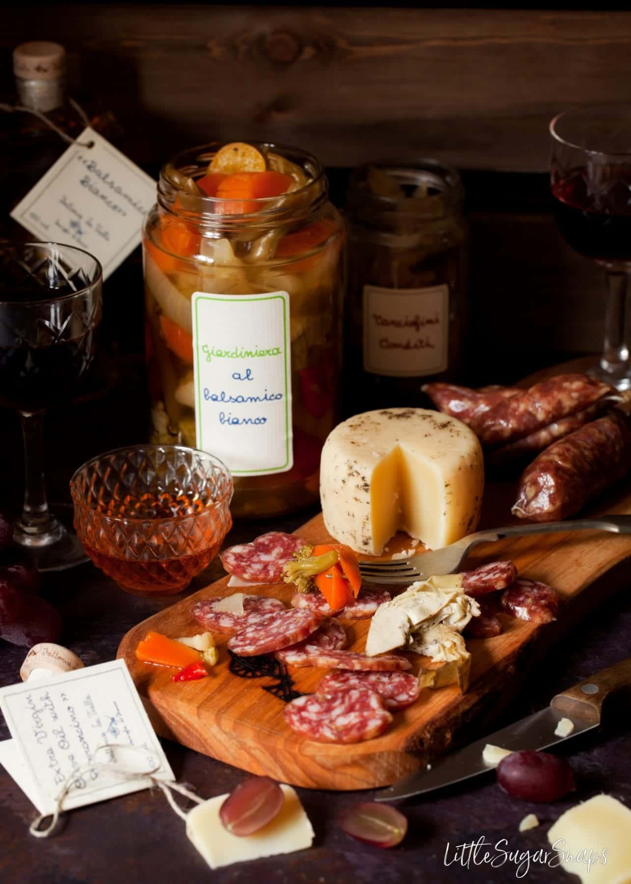 Fattoria La Vialla Products including pecorino cheese and fennel salami on a serving board with an open jar of picked vegetables