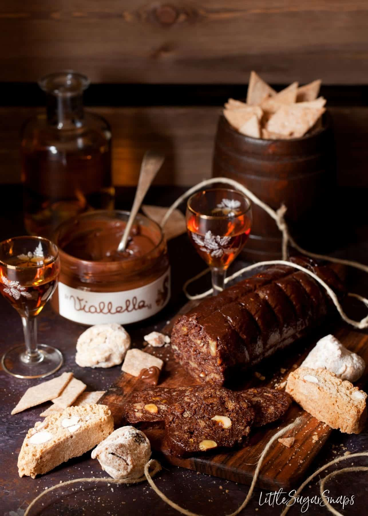 Chocolate salami, chocolate spread and biscuits on a serving board with a glass of vin santo