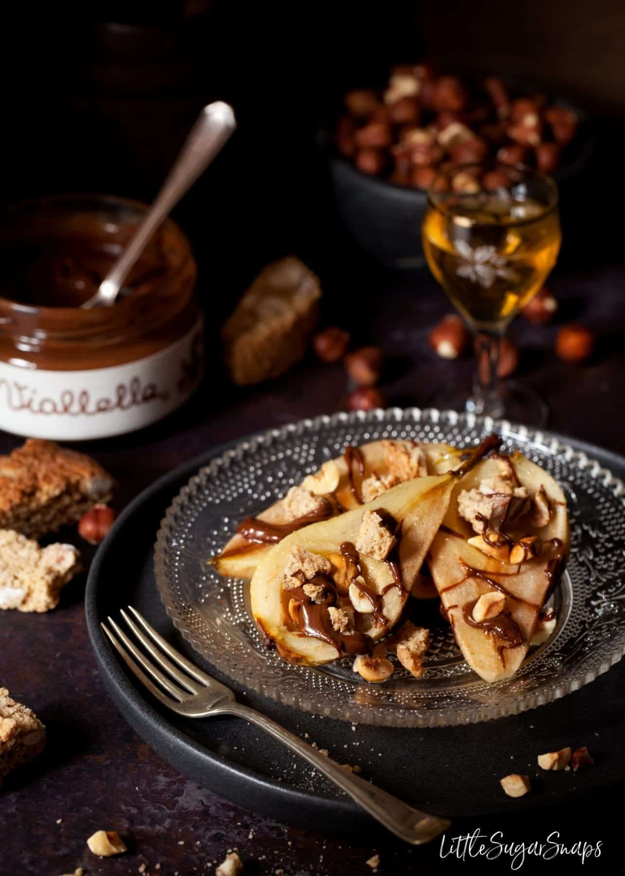Honey Baked Pears with Chocolate, cantucci biscuits on a plate with a glass of vin santo and a jar of chocolate sauce