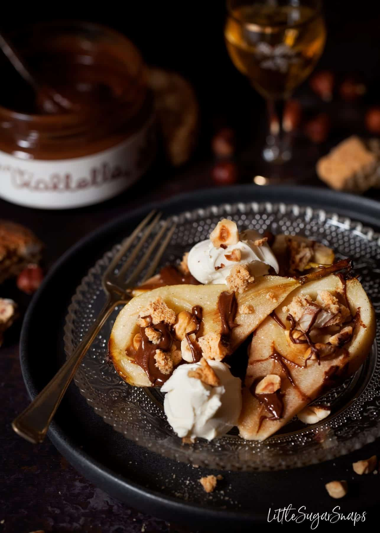 Honey Baked Pears with Chocolate, hazelnuts and cookies served on a plate with scoops of mascarpone cream cheese